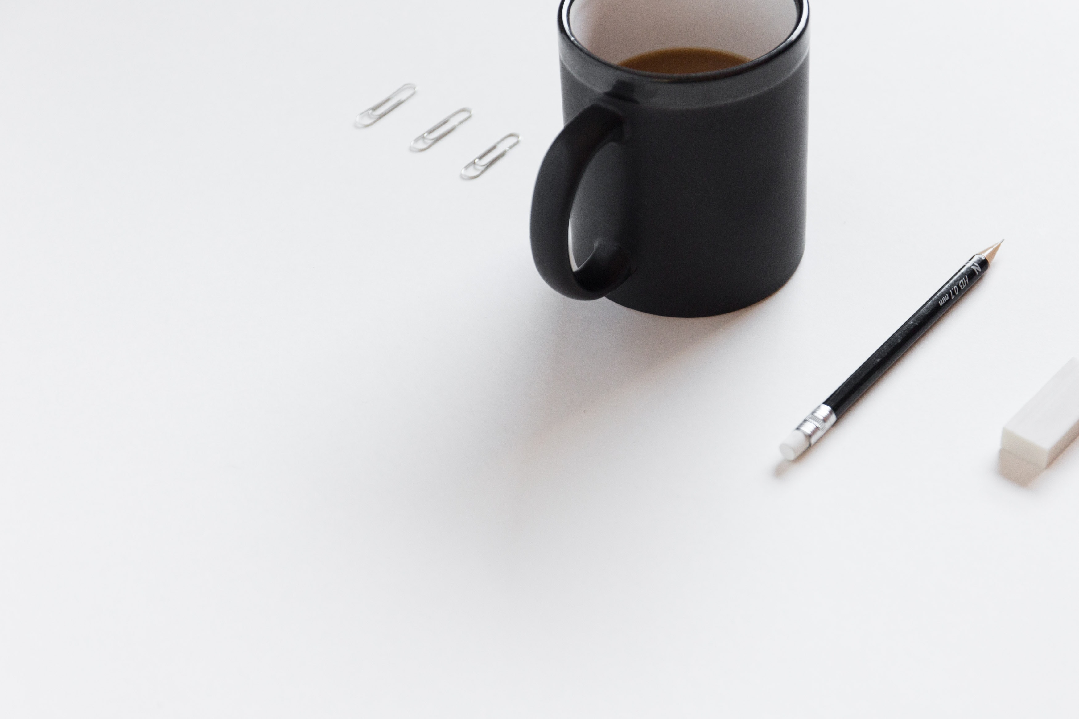 three white paper clips, black ceramic mug, black pencil, and white pencil eraser on white surface