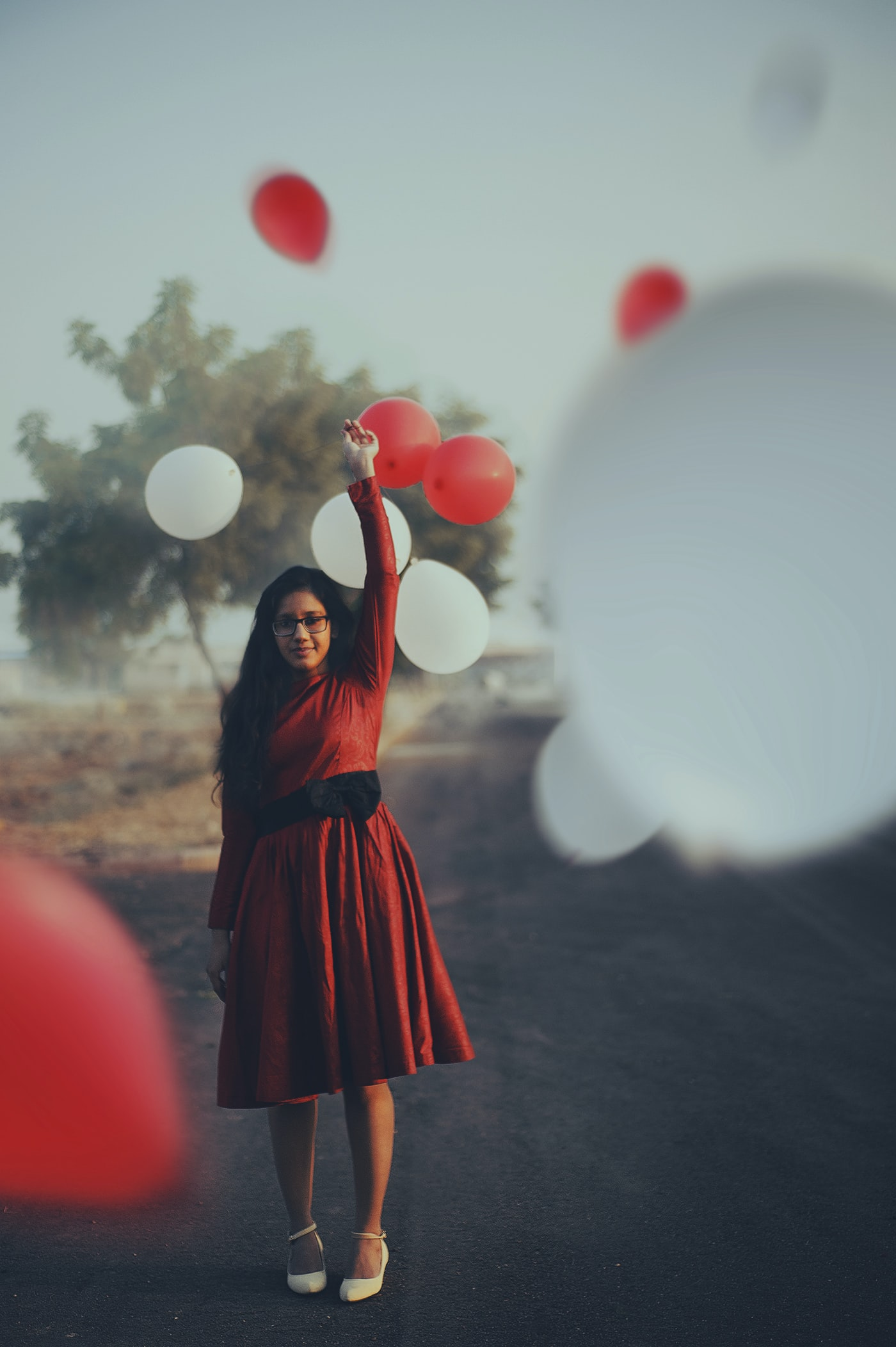 Young woman holds a balloon surrounded by red and white balloons