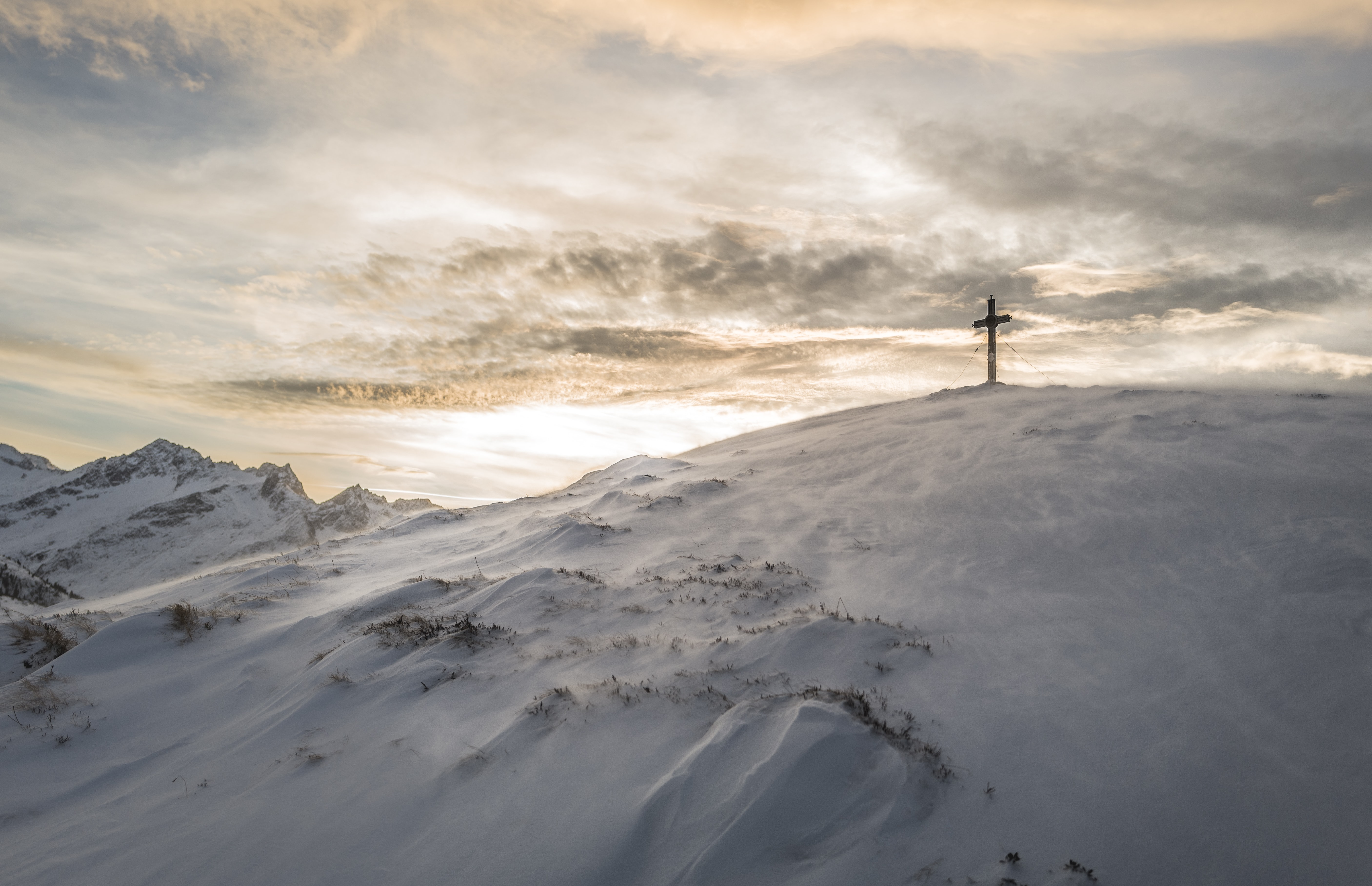 A cross at the top of a snowy mountain backlit by a setting or rising sun