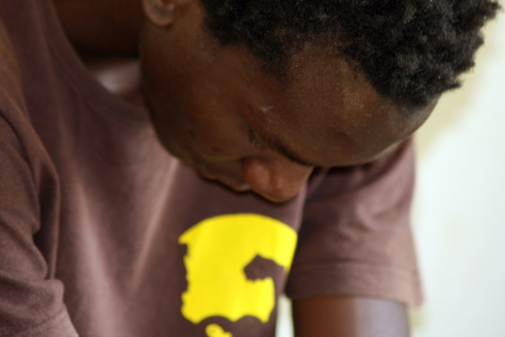 An African American man looking down at his hands while sitting for a prayer.