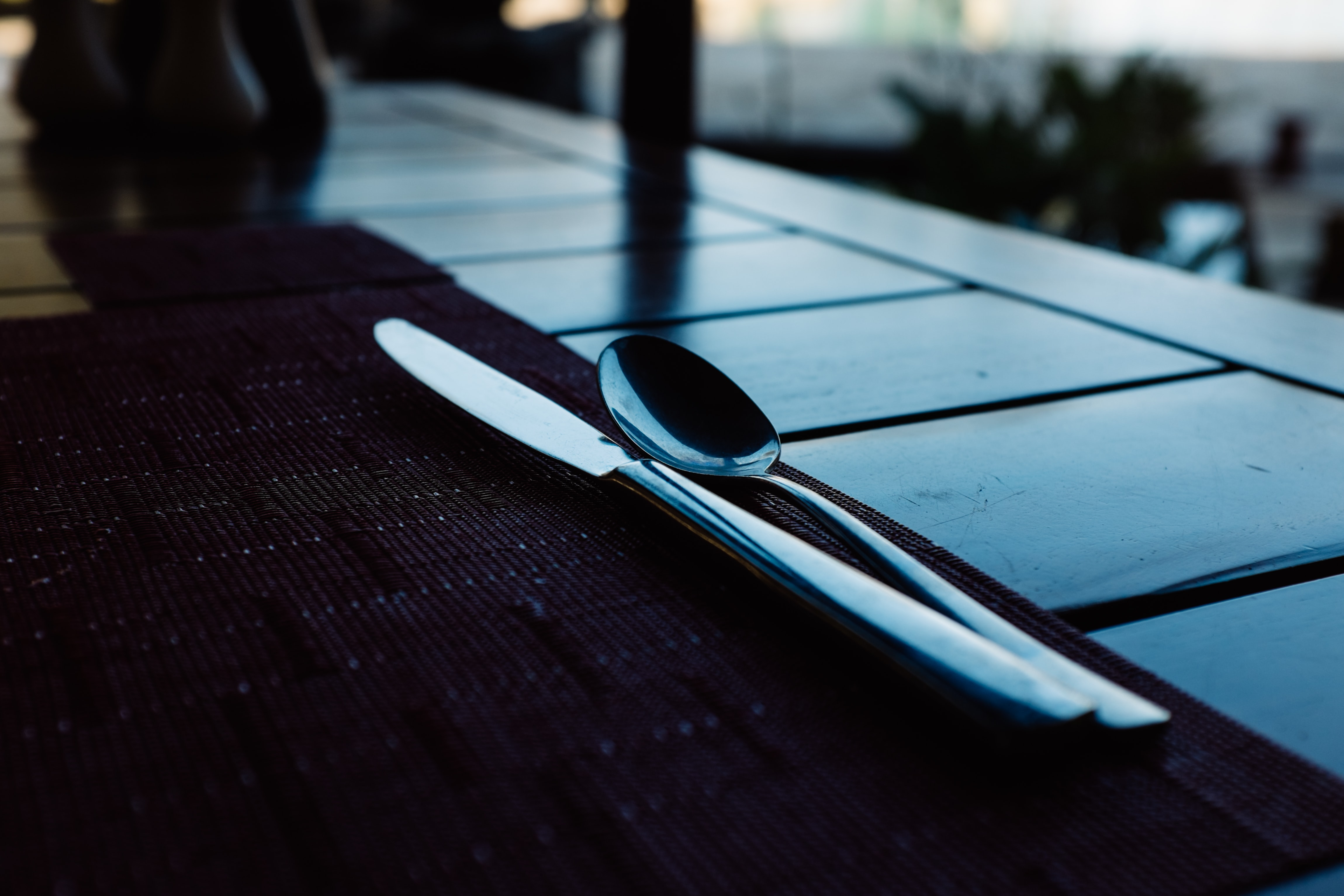 Macro of shiny knife and spoon on a placemat near a window on a slatted table