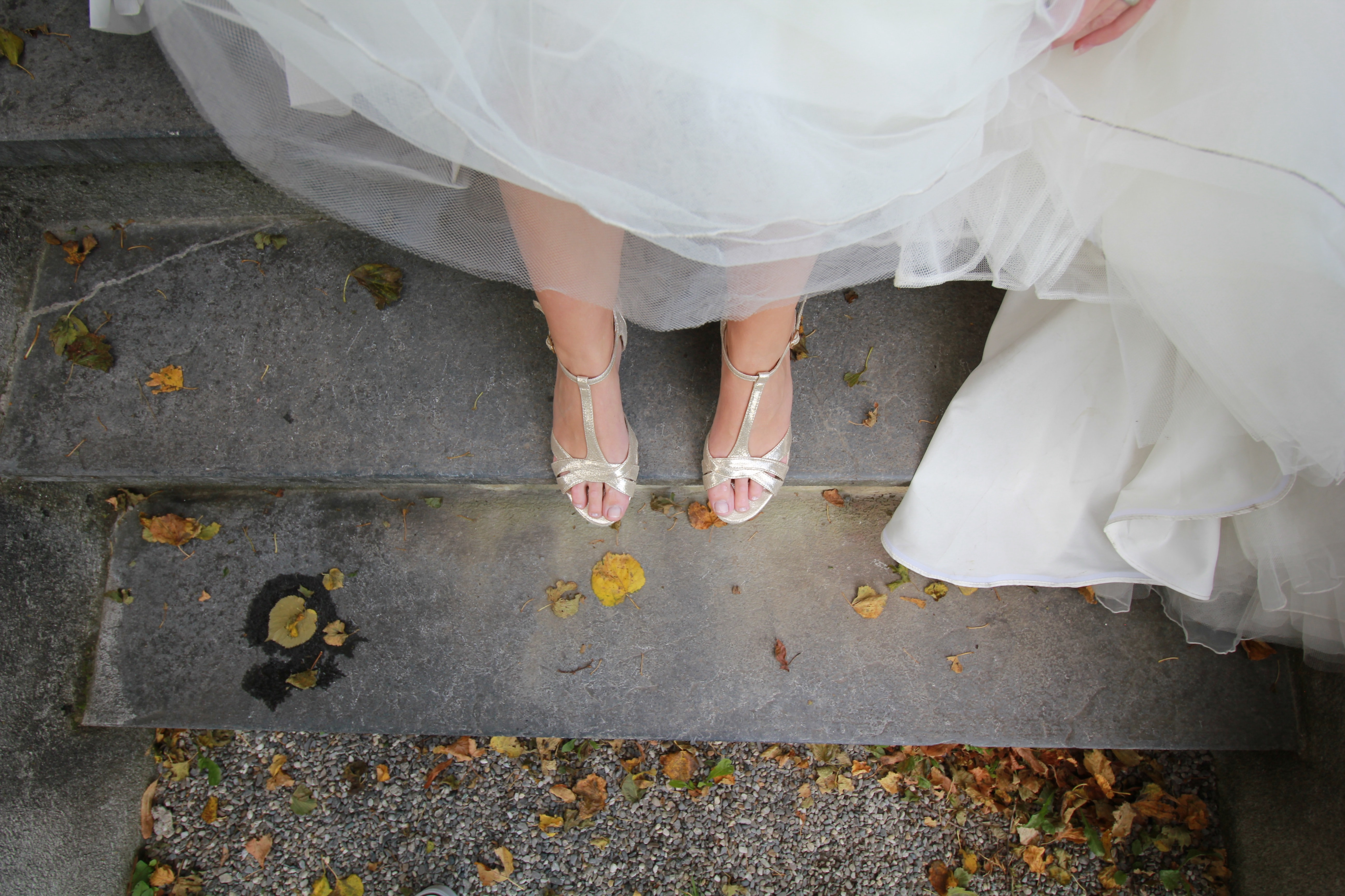 Bride wearing silver wedding shoes stands on stone steps in Zizers