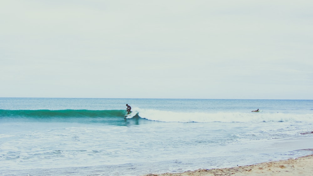 person surfing using white surfboard during daytime