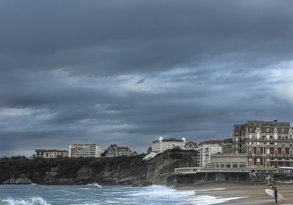 concrete buildings by the sea during daytime