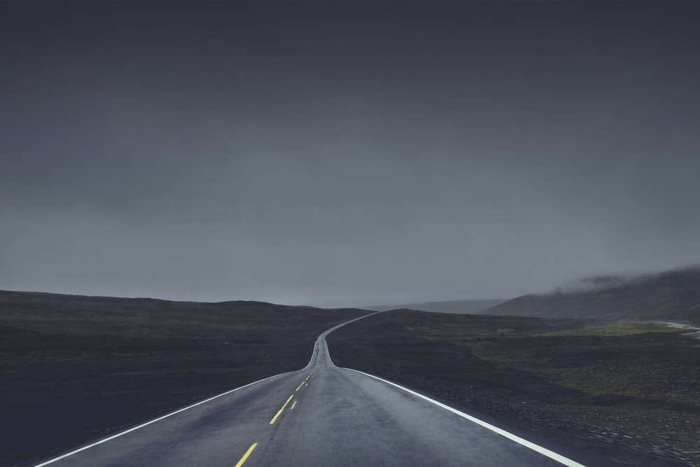 photography of road under cloudy sky