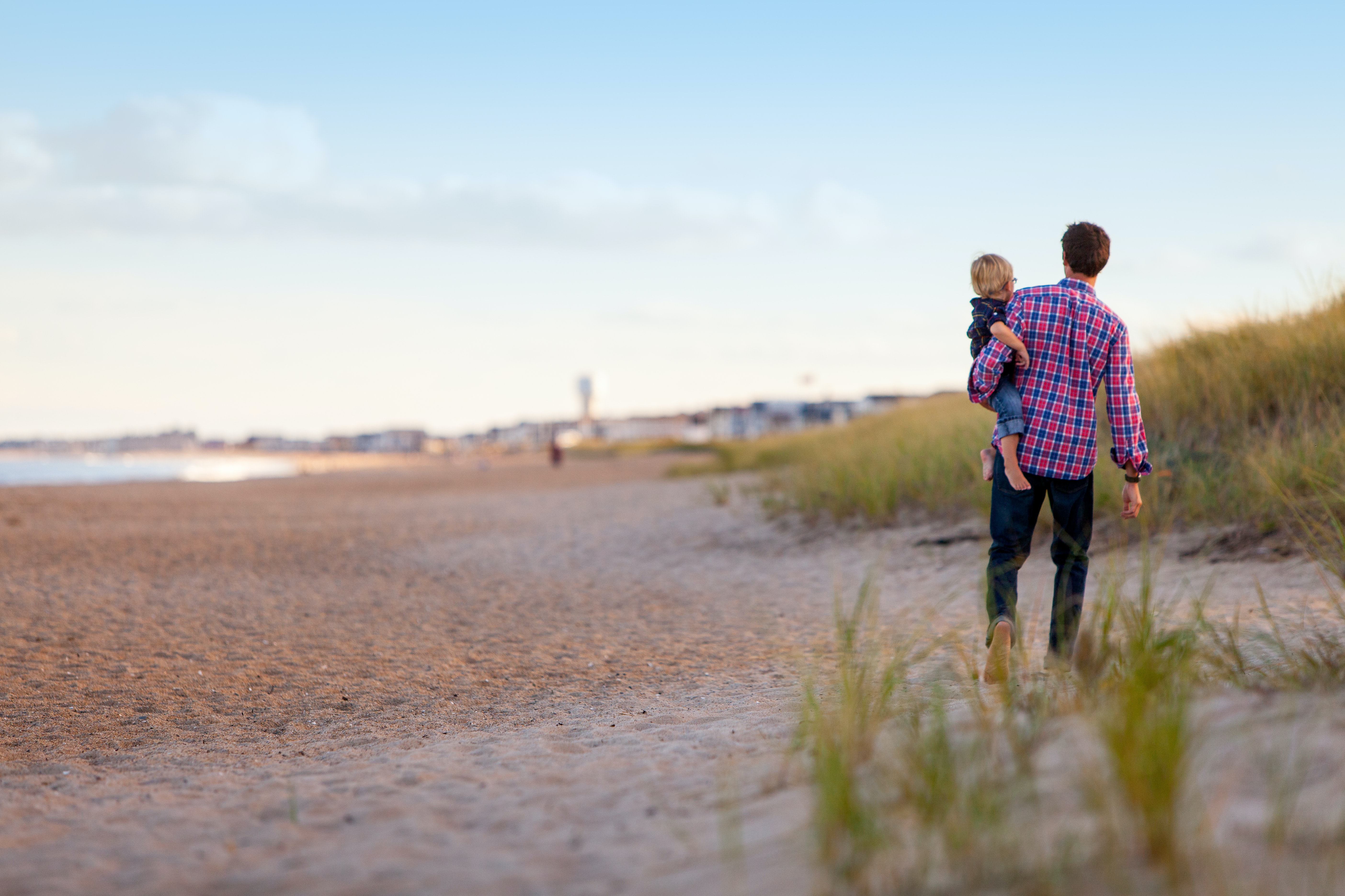 Father in plaid shirt and jeans holds child on hip as they walk along the dunes