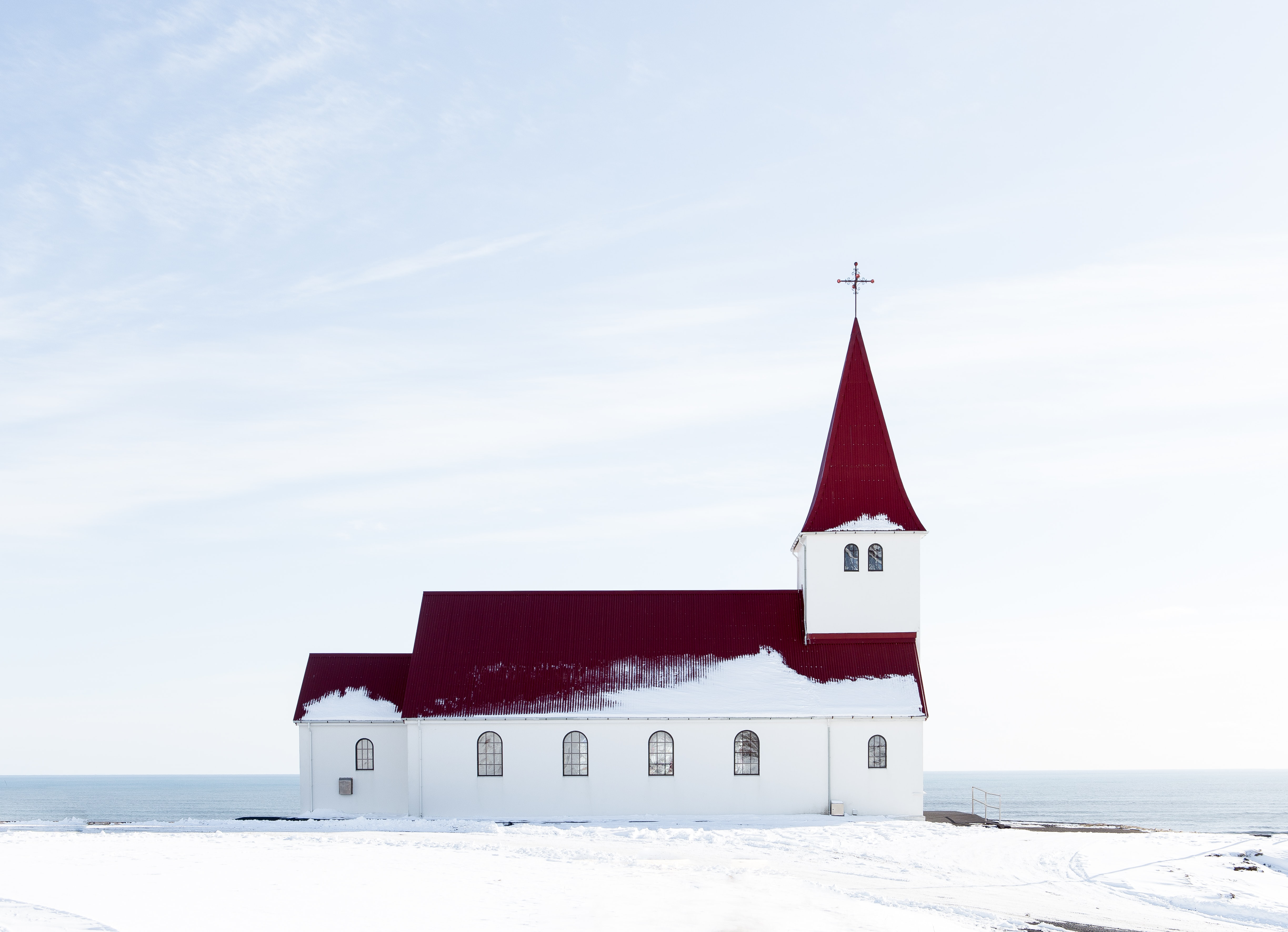 A white church with dark red roof in a stark, snowy setting