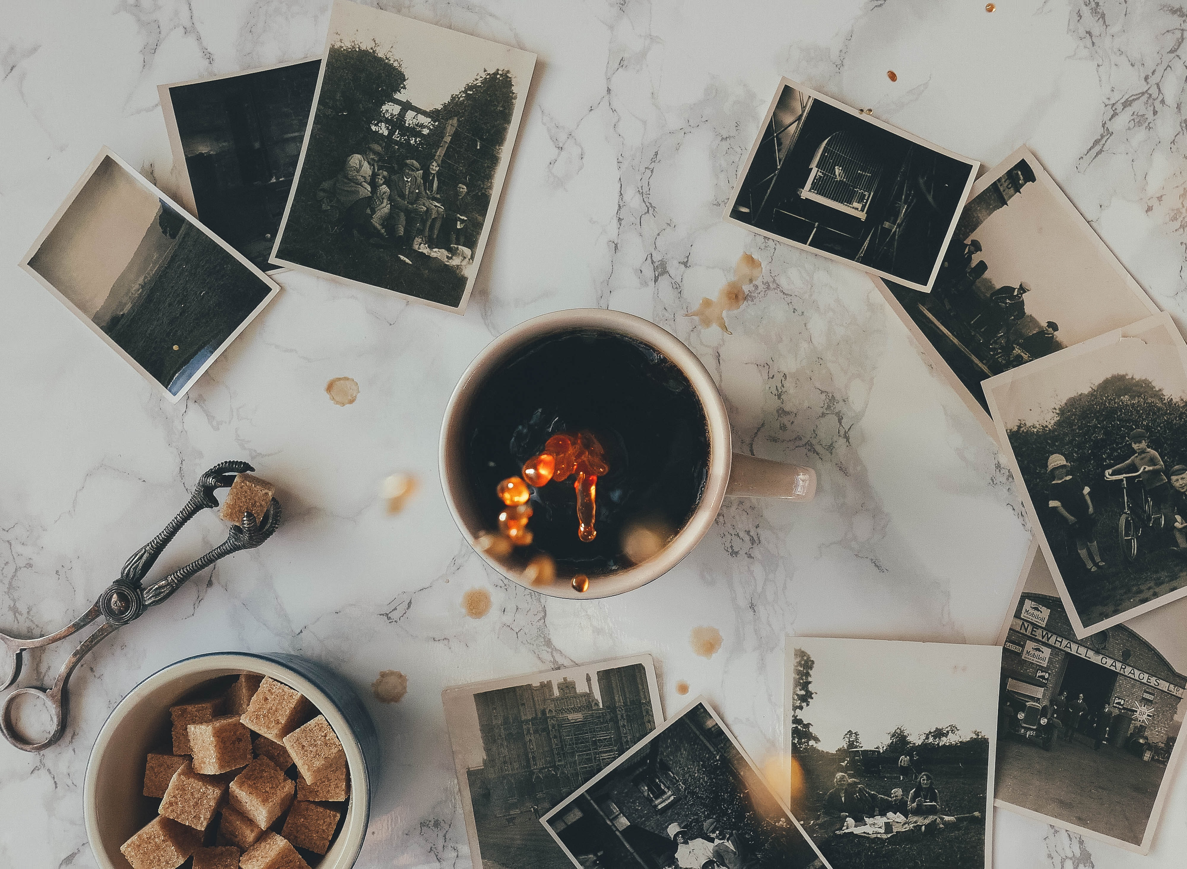 A flatlay with a cup of coffee, brown sugar cubes and black-and-white photographs