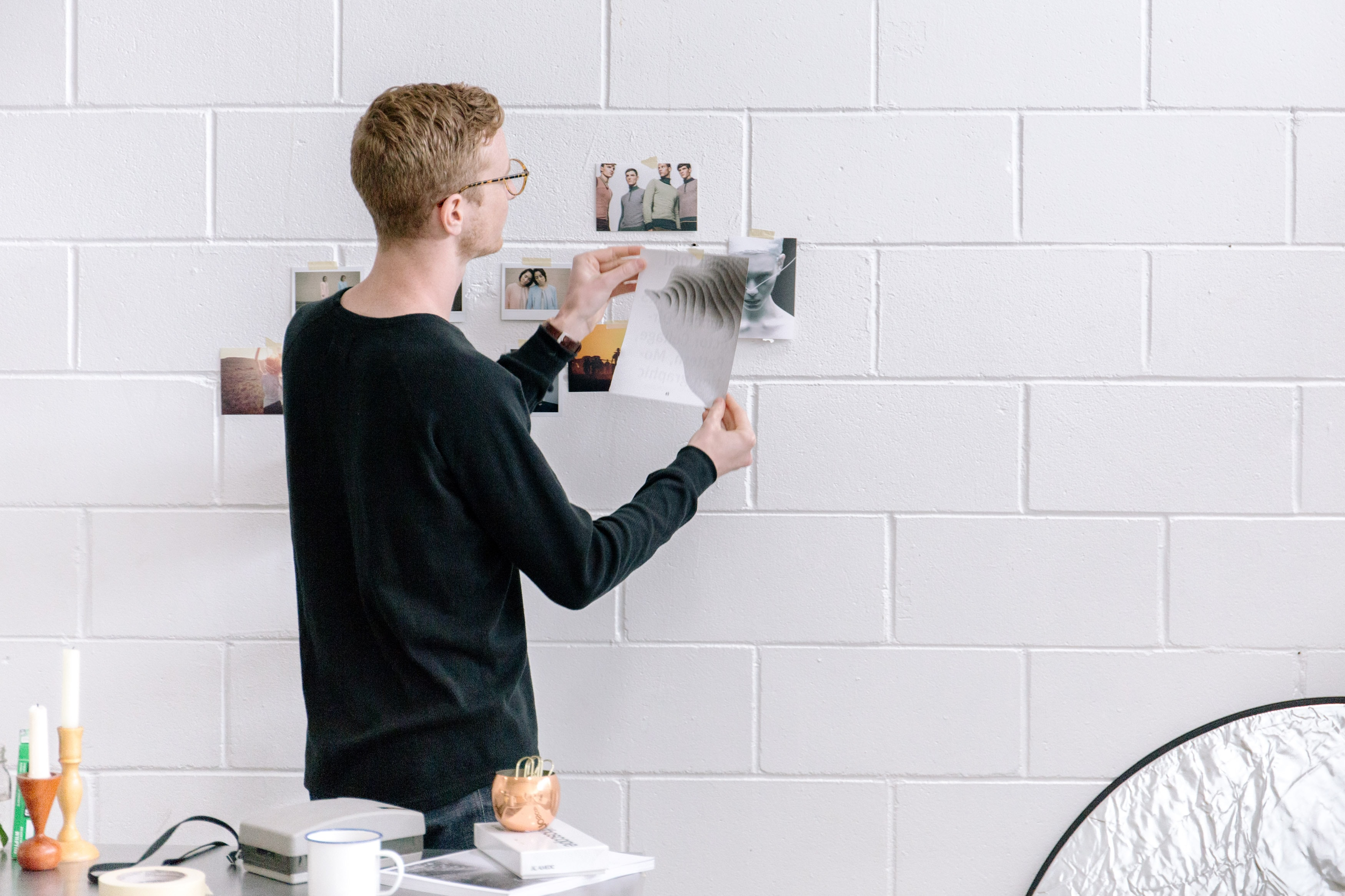 A young man hanging photos on a white wall