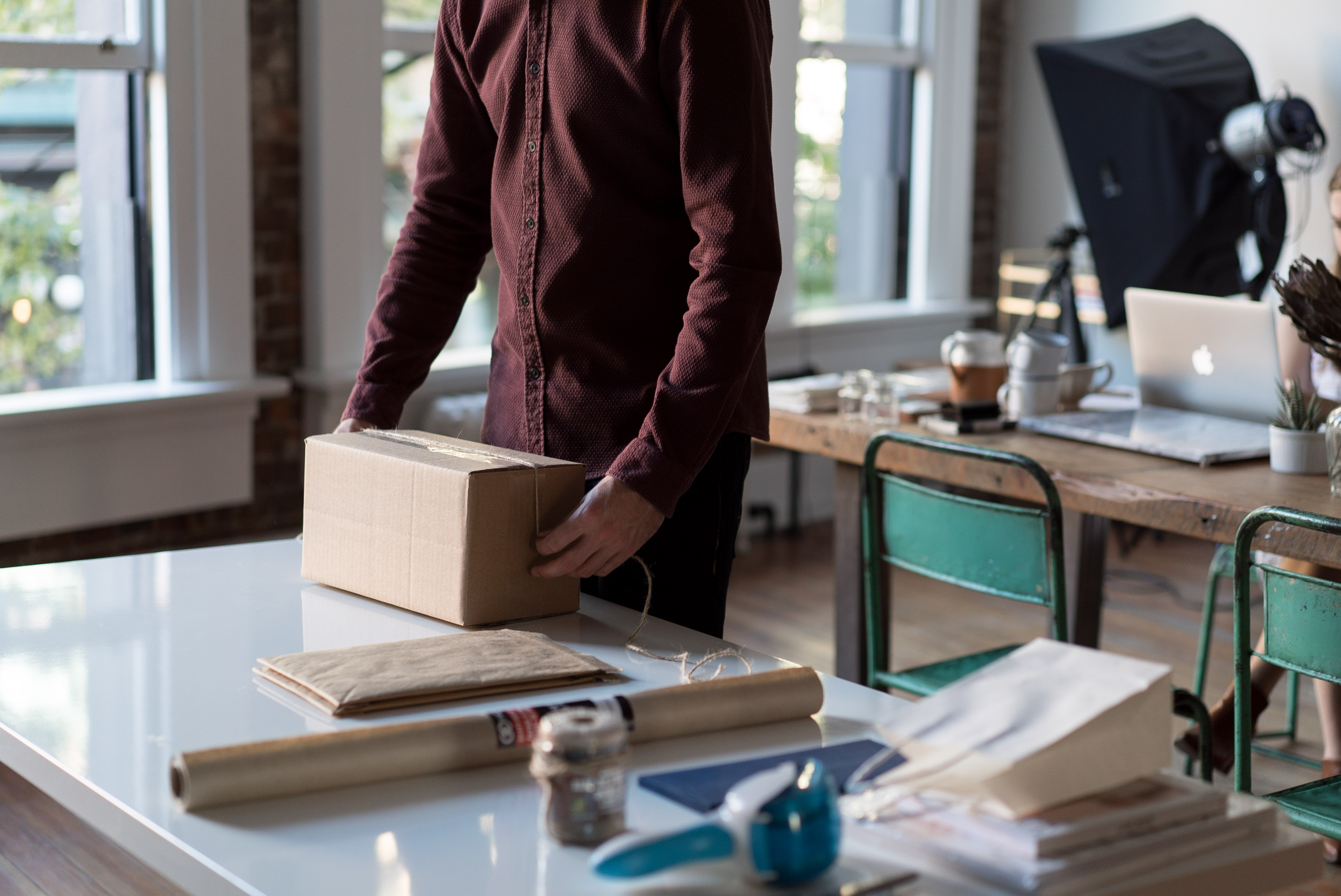 A man packing a cardboard box in a small office