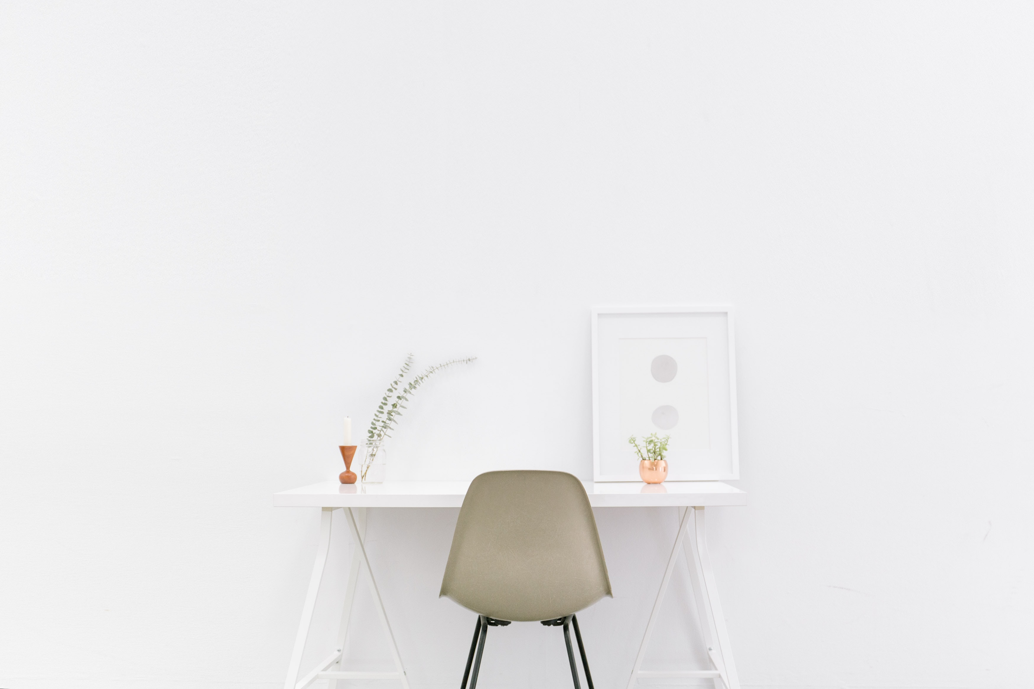 A beige chair at a small white desk with potted plants and framed art