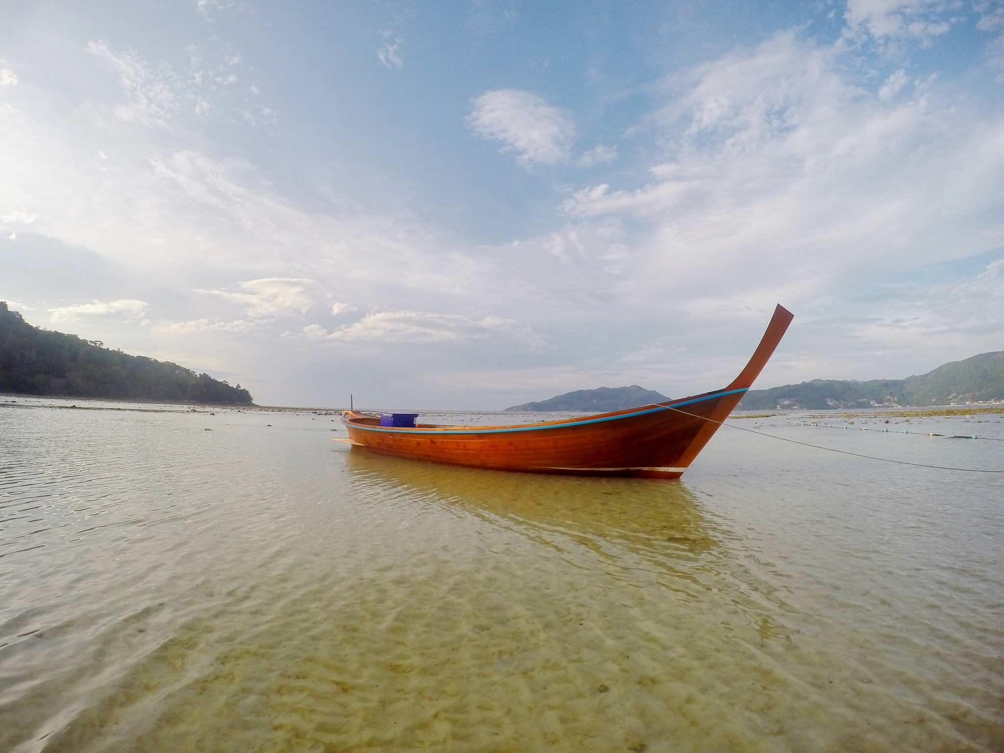 A red boat sitting in water near the shore.