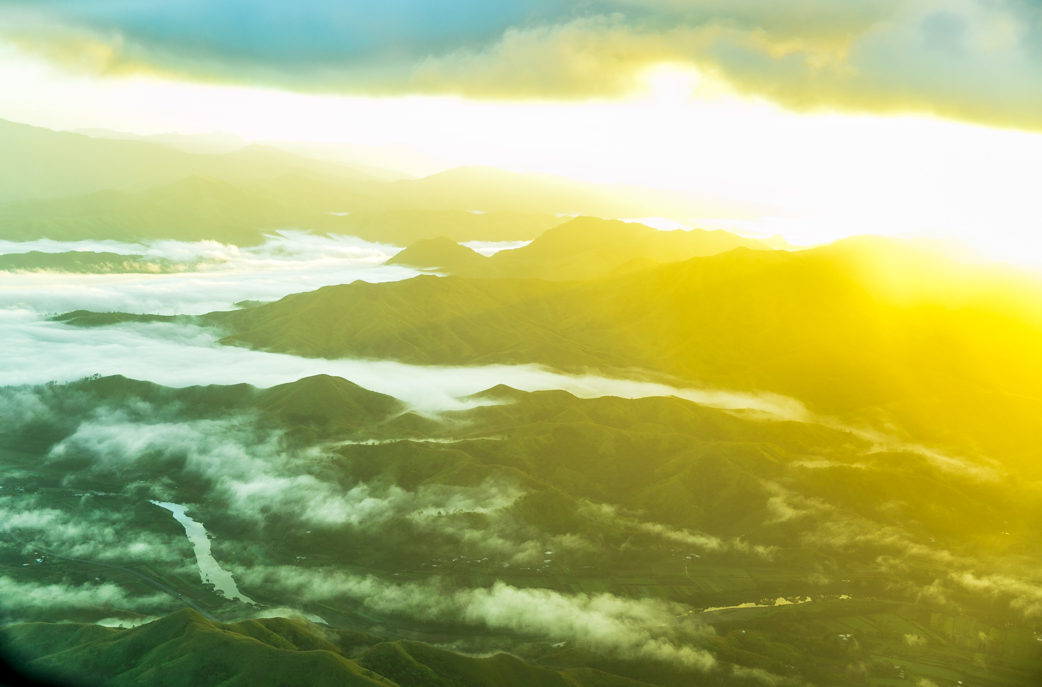 Colorful sun rises over foggy mountainscape in Suva Fiji