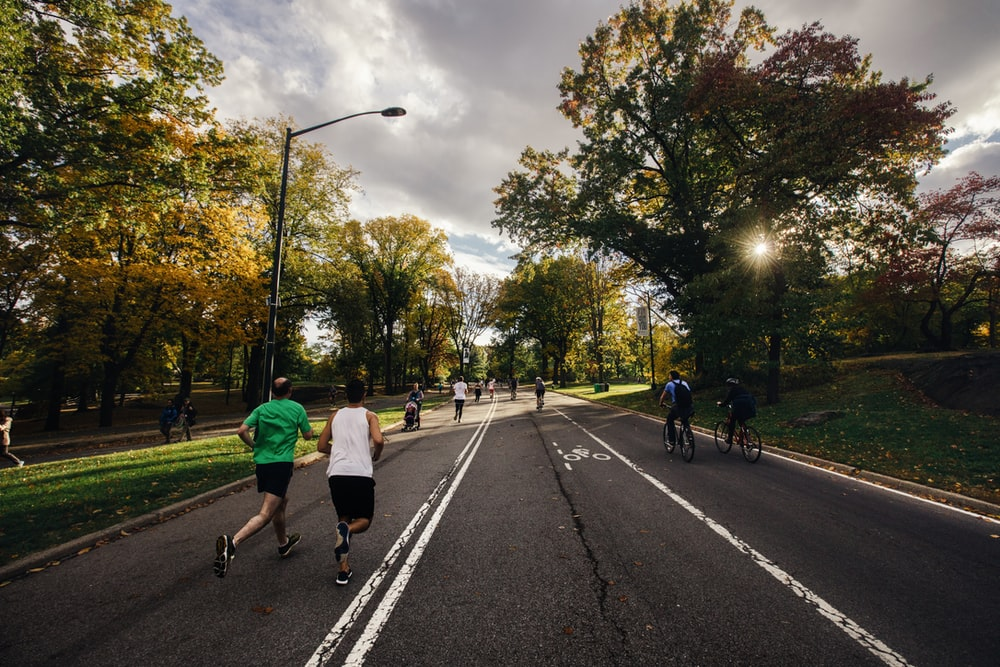 people running and riding bicycle