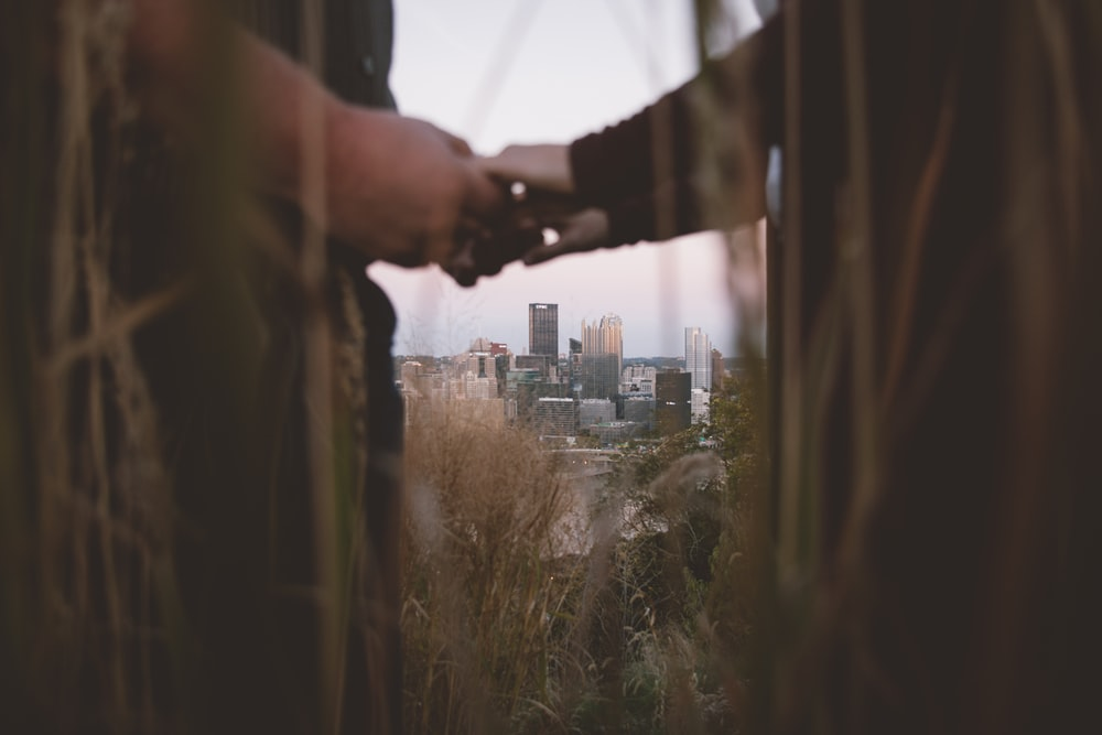 couple holding hands in a distance of city