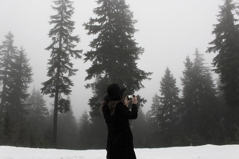 woman takes photo at the snowfield surrounded with trees