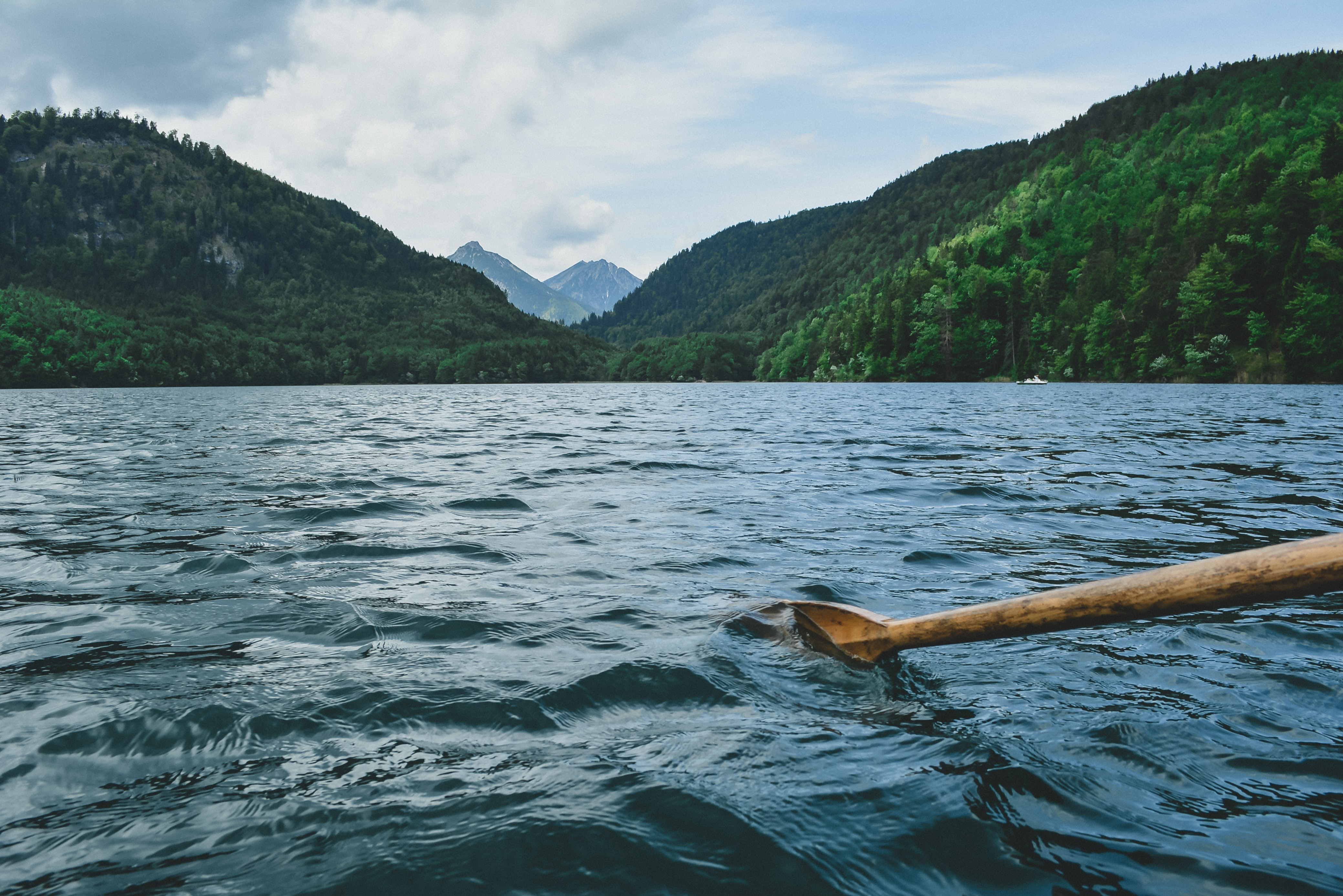 A boat view of a wooden oar in water on a choppy lake in the mountains