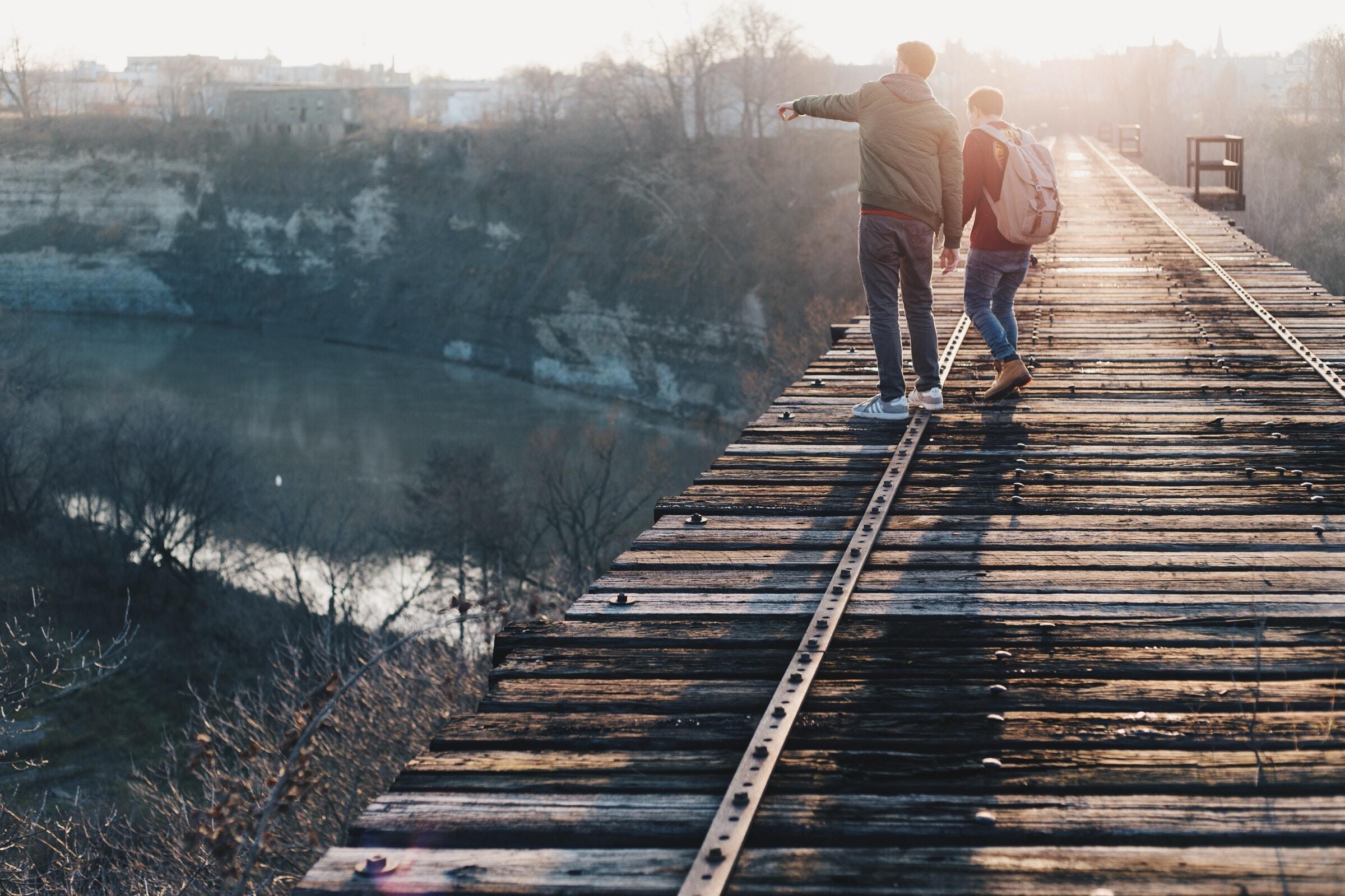 two boy standing on brown train track bridge near river