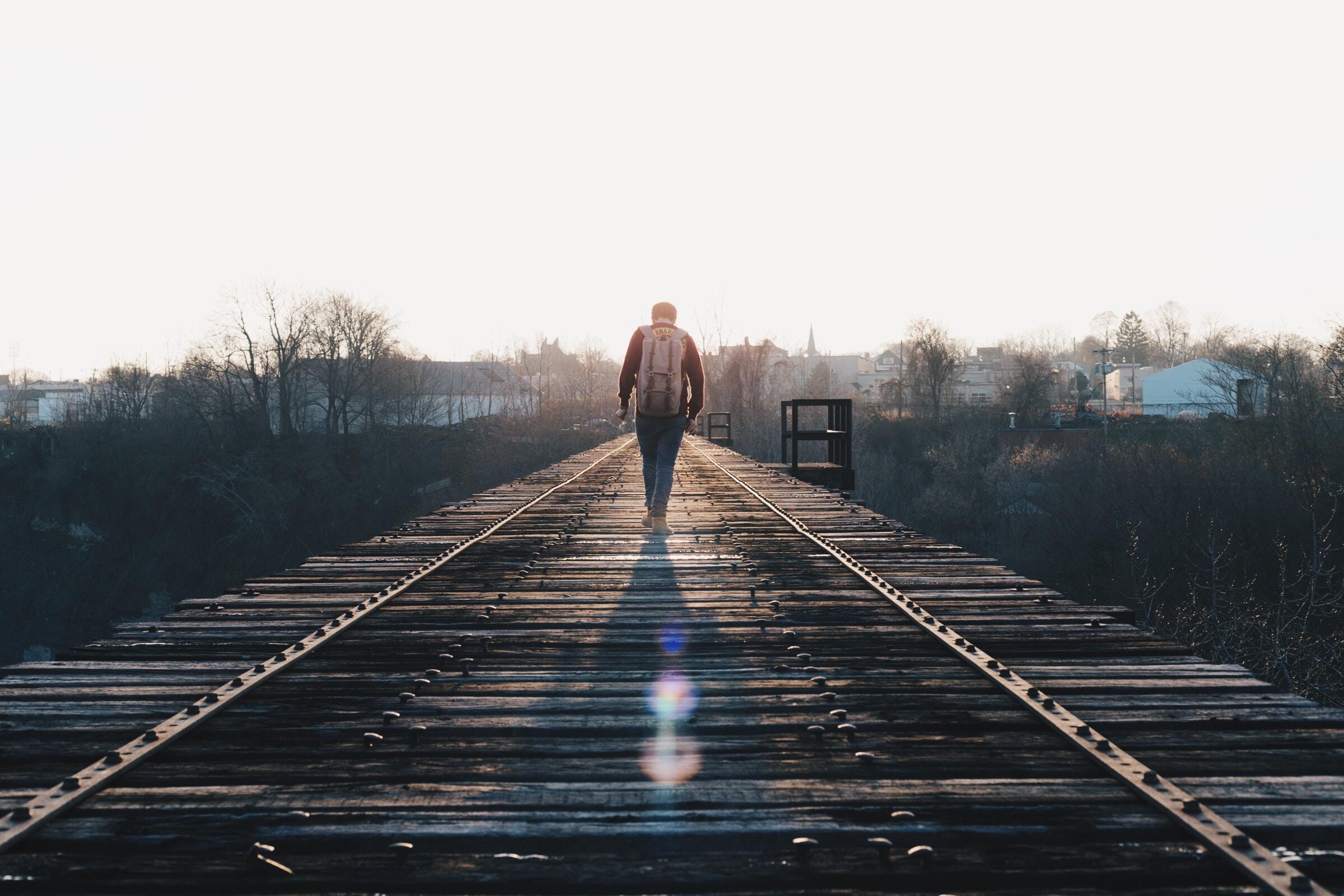 A man wearing a backpack walking across a railroad bridge in Rochester