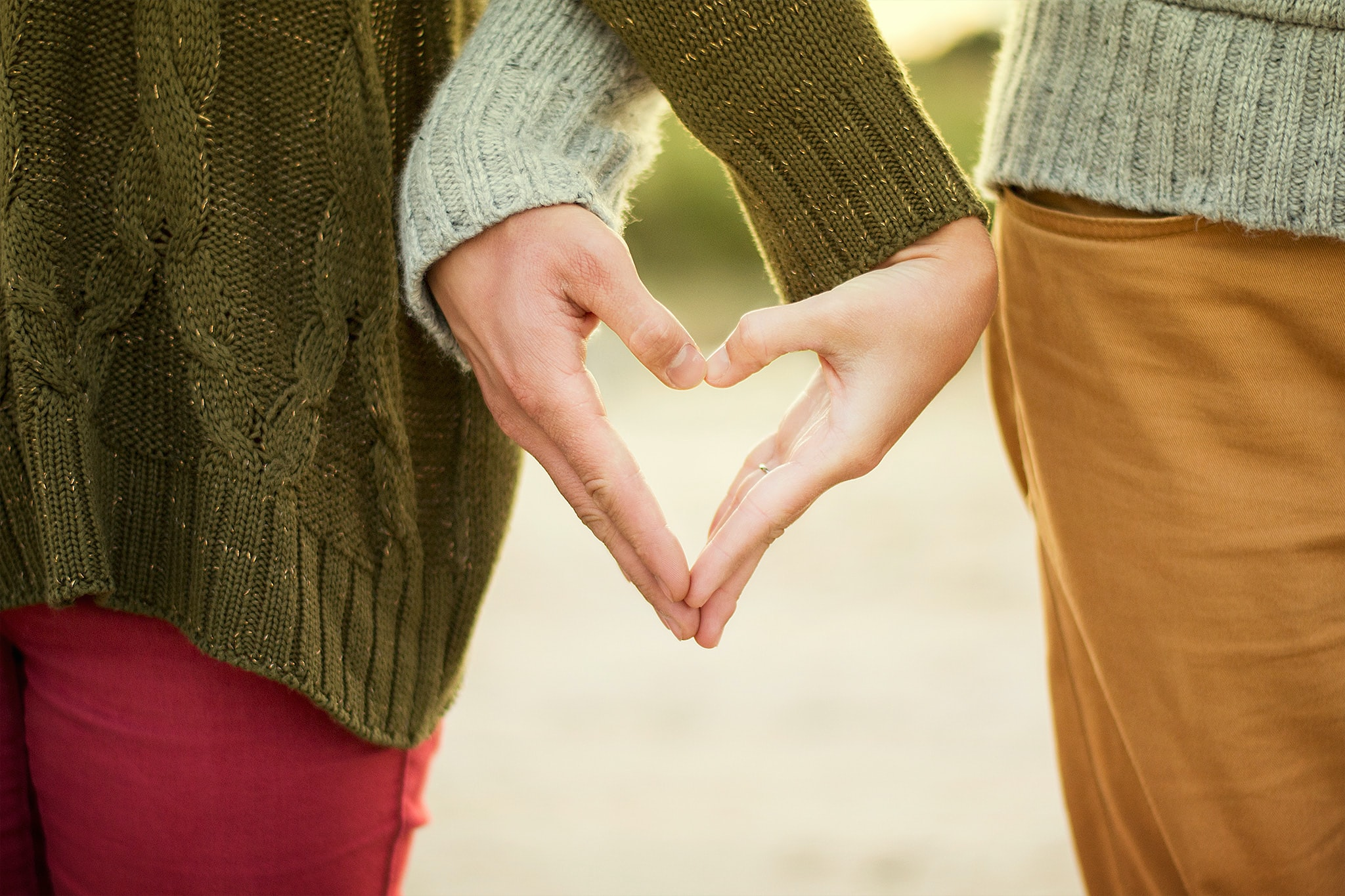 Close-up of couple's hands intertwined to create a heart shape