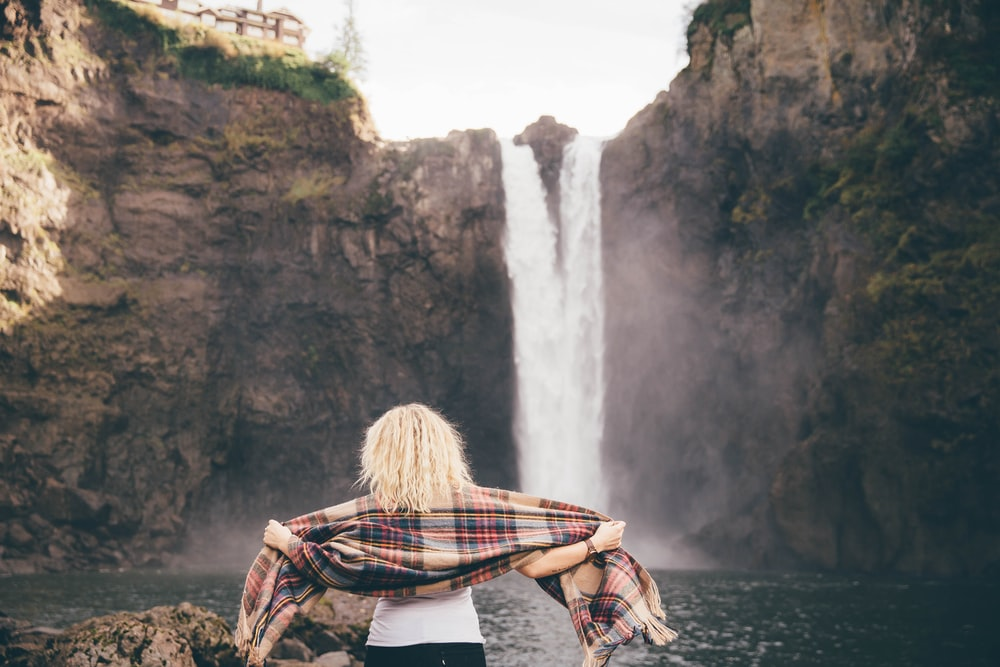 woman standing on stone beside the waterfalls