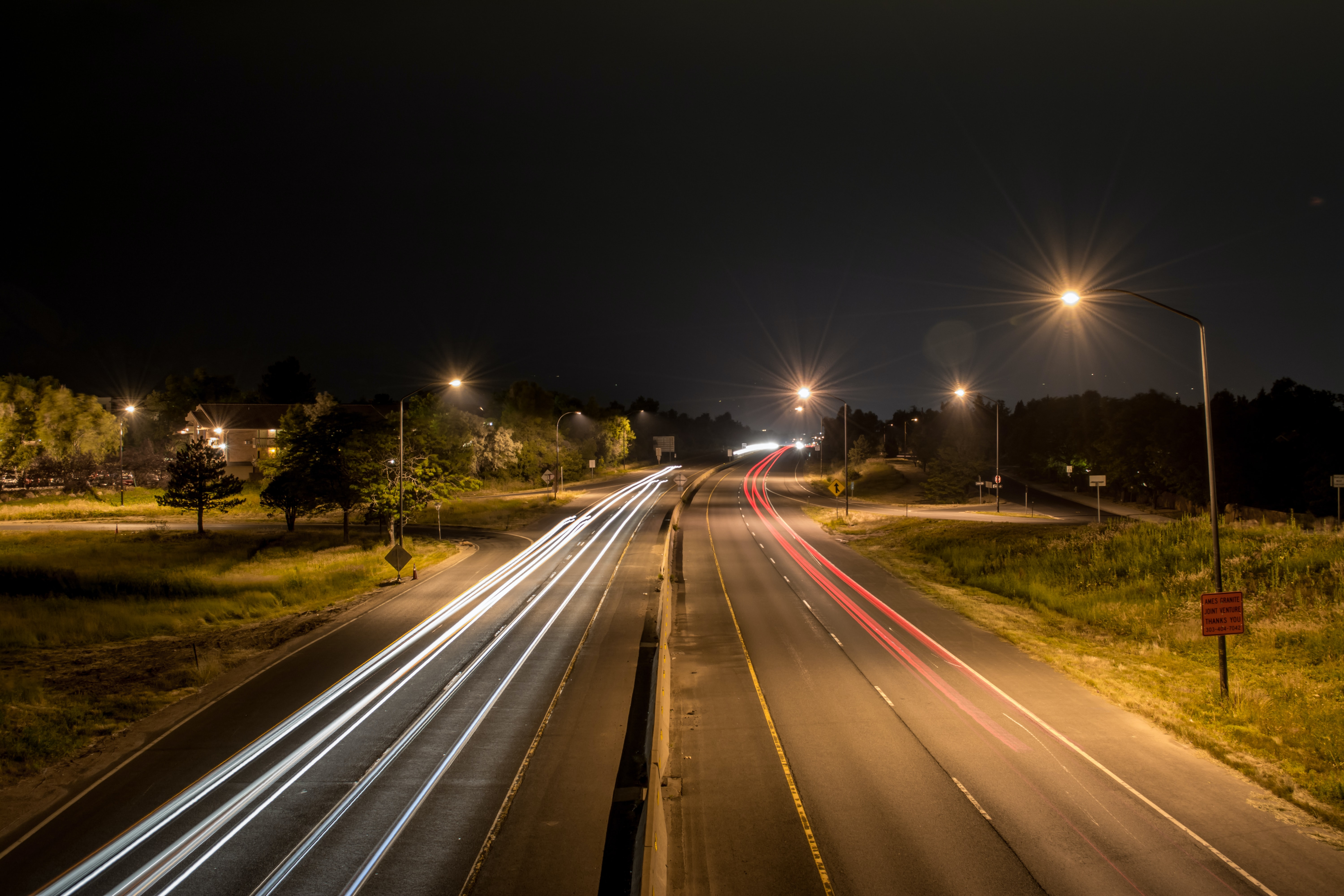 Car lights form streaks of red on busy city street at night