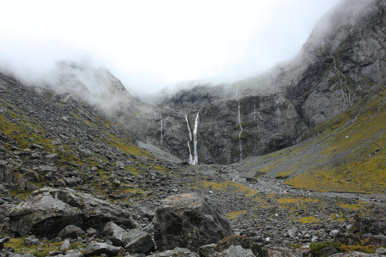 Waterfalls on a foggy rocky facade in New Zealand