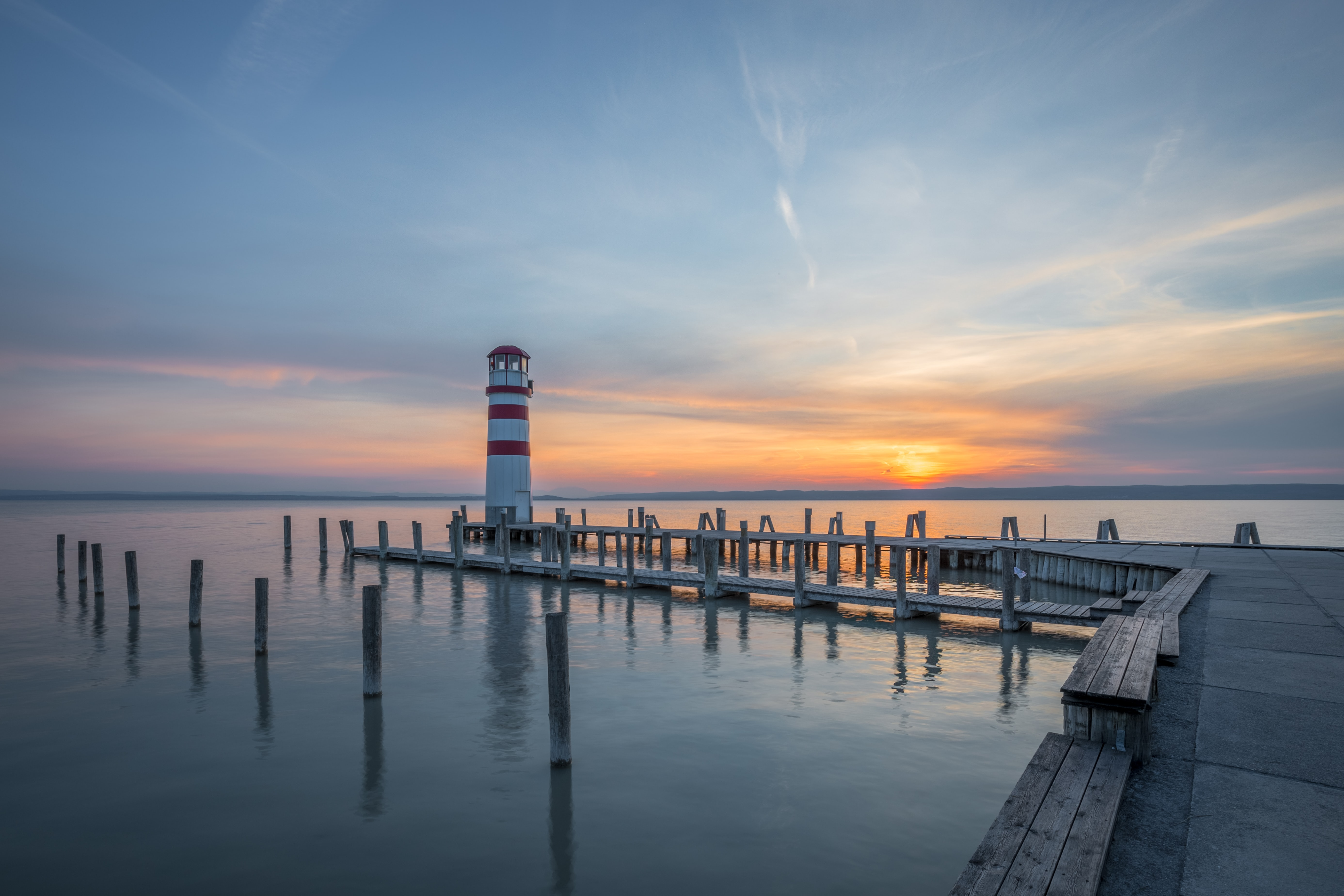 lighthouse at end of docks under clear sky during sunrise