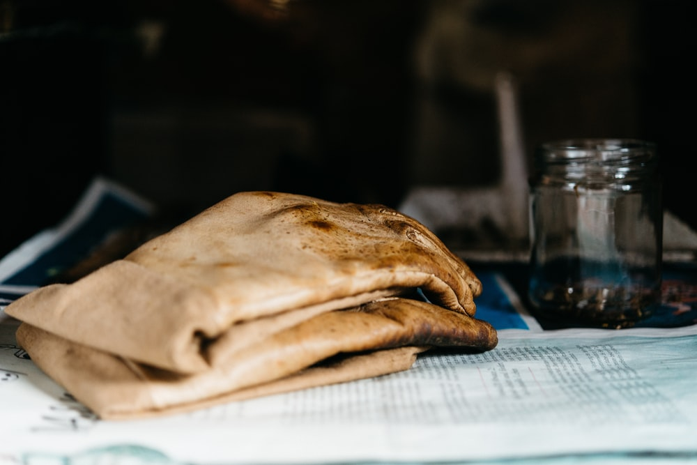pair of brown leather gloves beside glass jar on newspaper