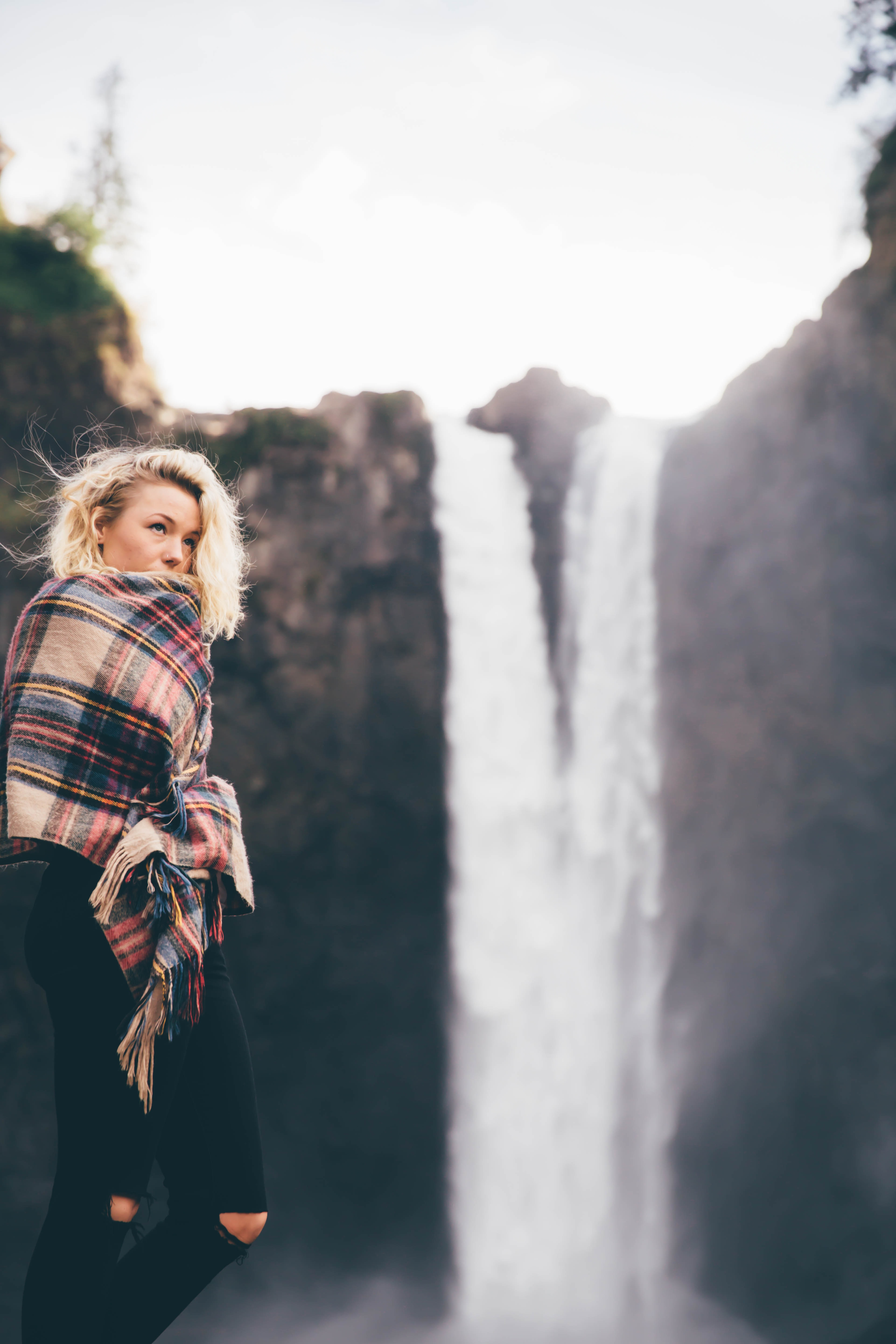 A woman wrapped in a plaid scarf or blanket standing on the edge of Snoqualmie Falls
