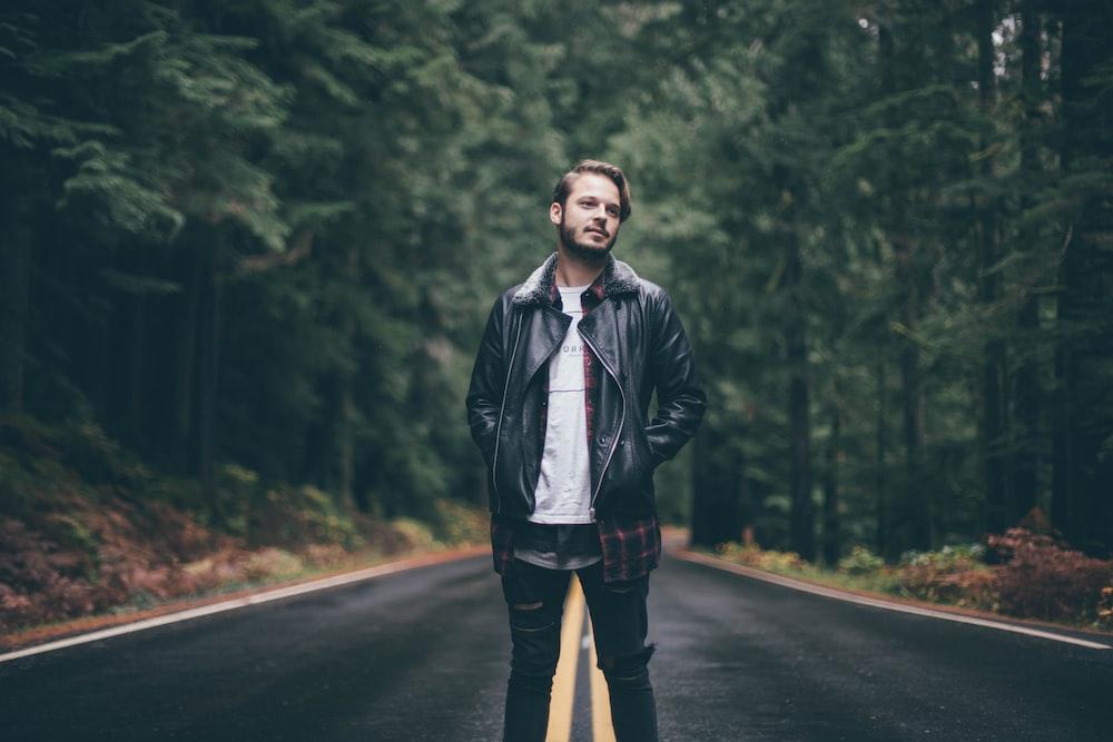 man wearing black zip-up jacket standing in middle of road