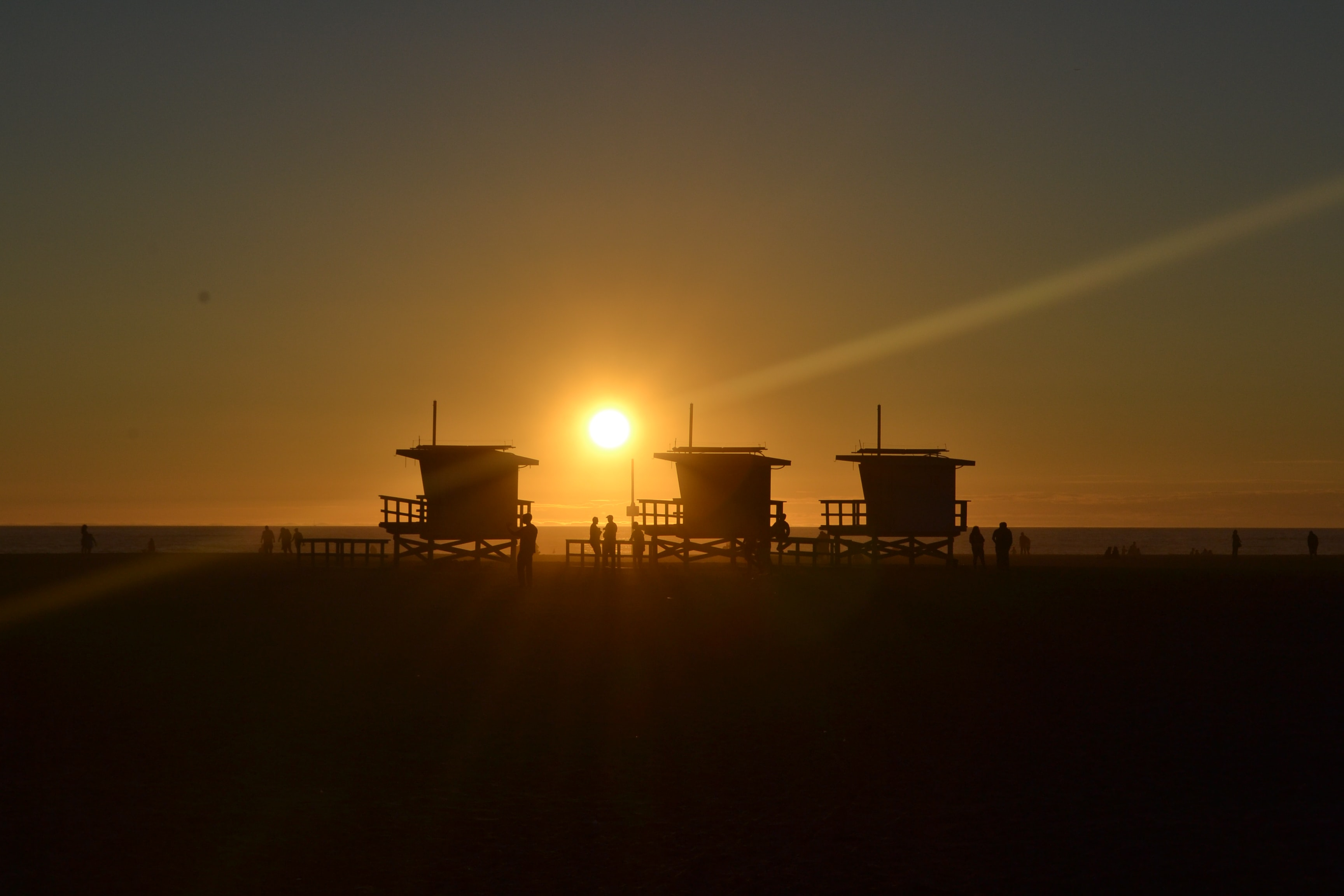 Sun setting behind the silhouettes of three lifeguard stations at Venice Beach