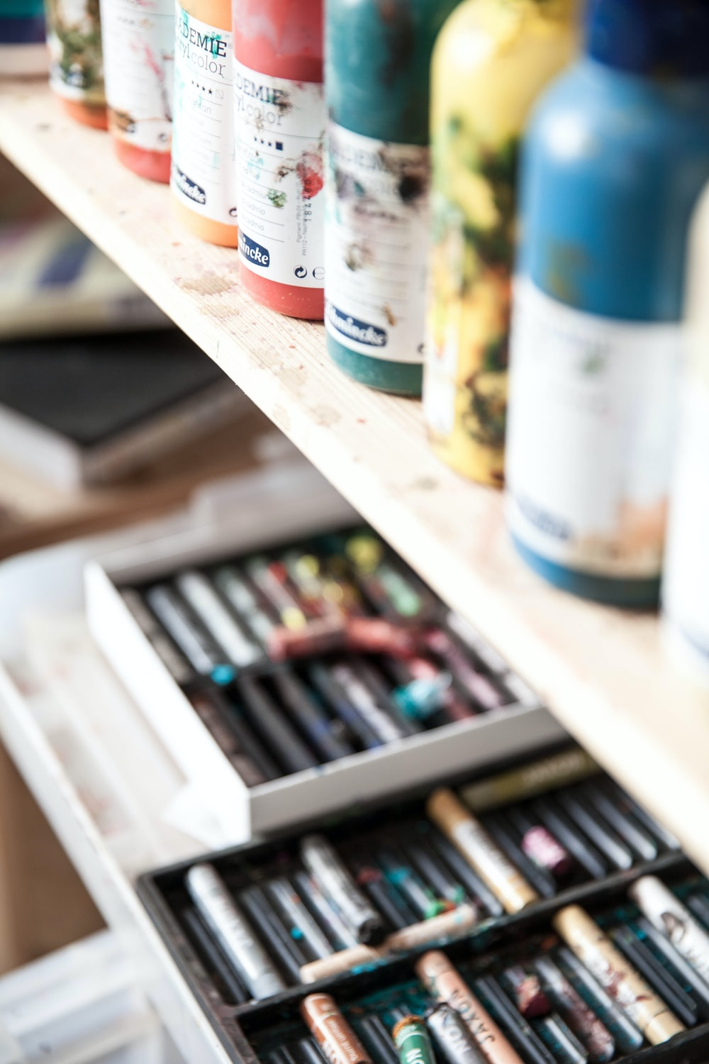 closeup photography of crayons and paint bottle