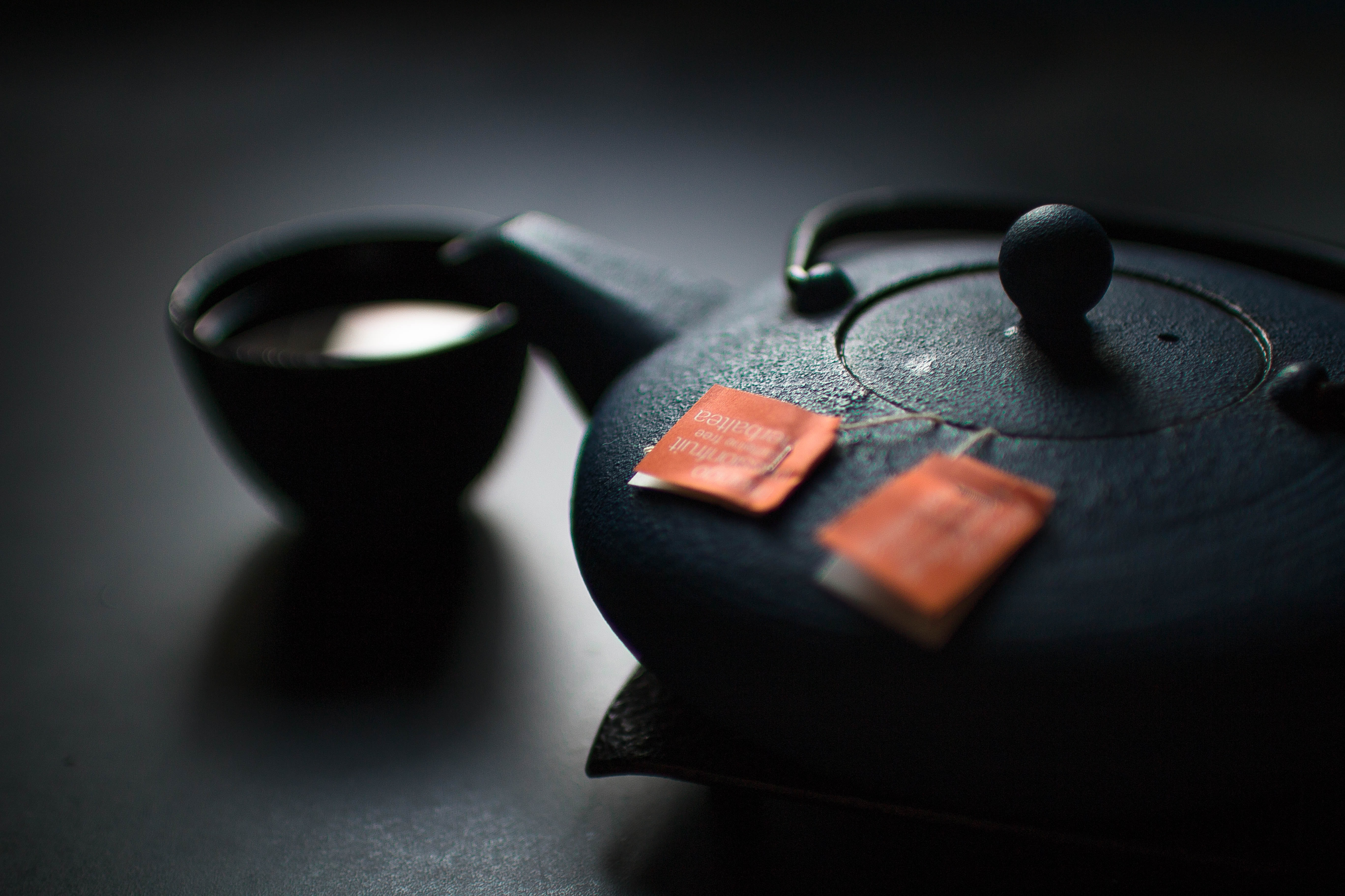 Two tea bags in the black ceramic tea pot with a cup