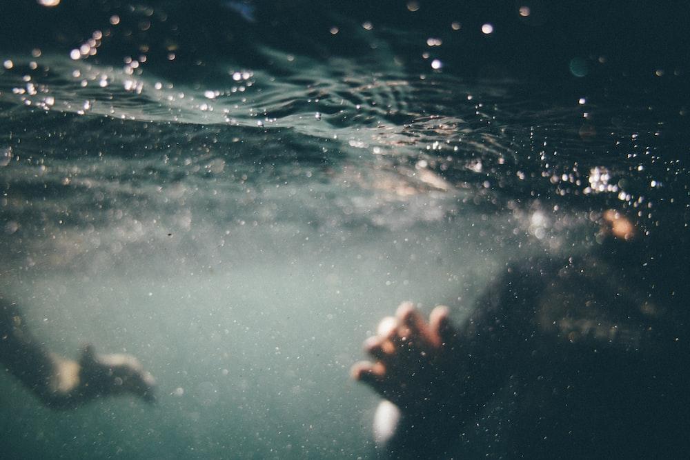 underwater photo of person wearing black shirt