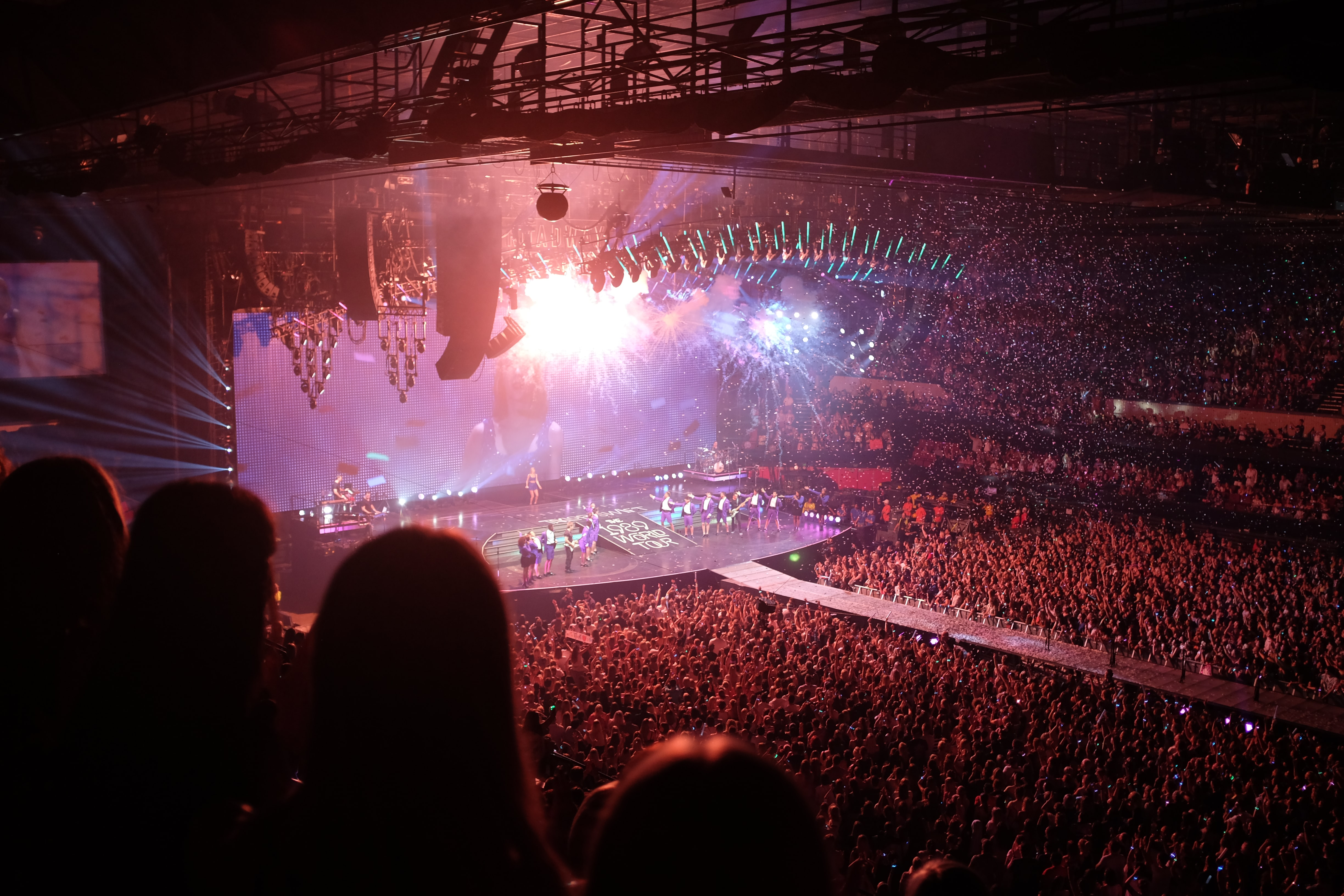 A high shot of a full concert hall with people lined up on the stage under bright lights