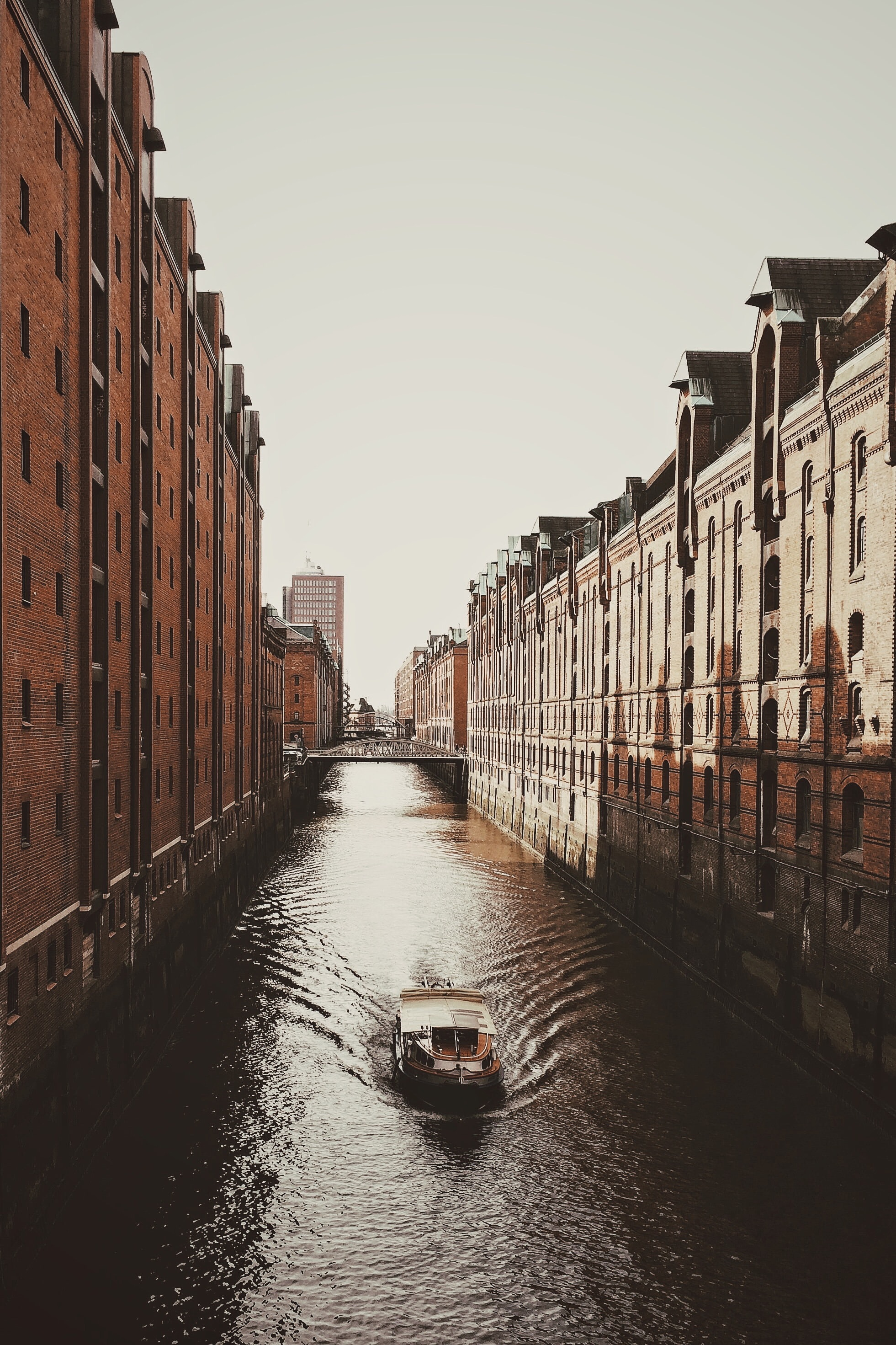 A boat on a canal in HafenCity on a cloudy day