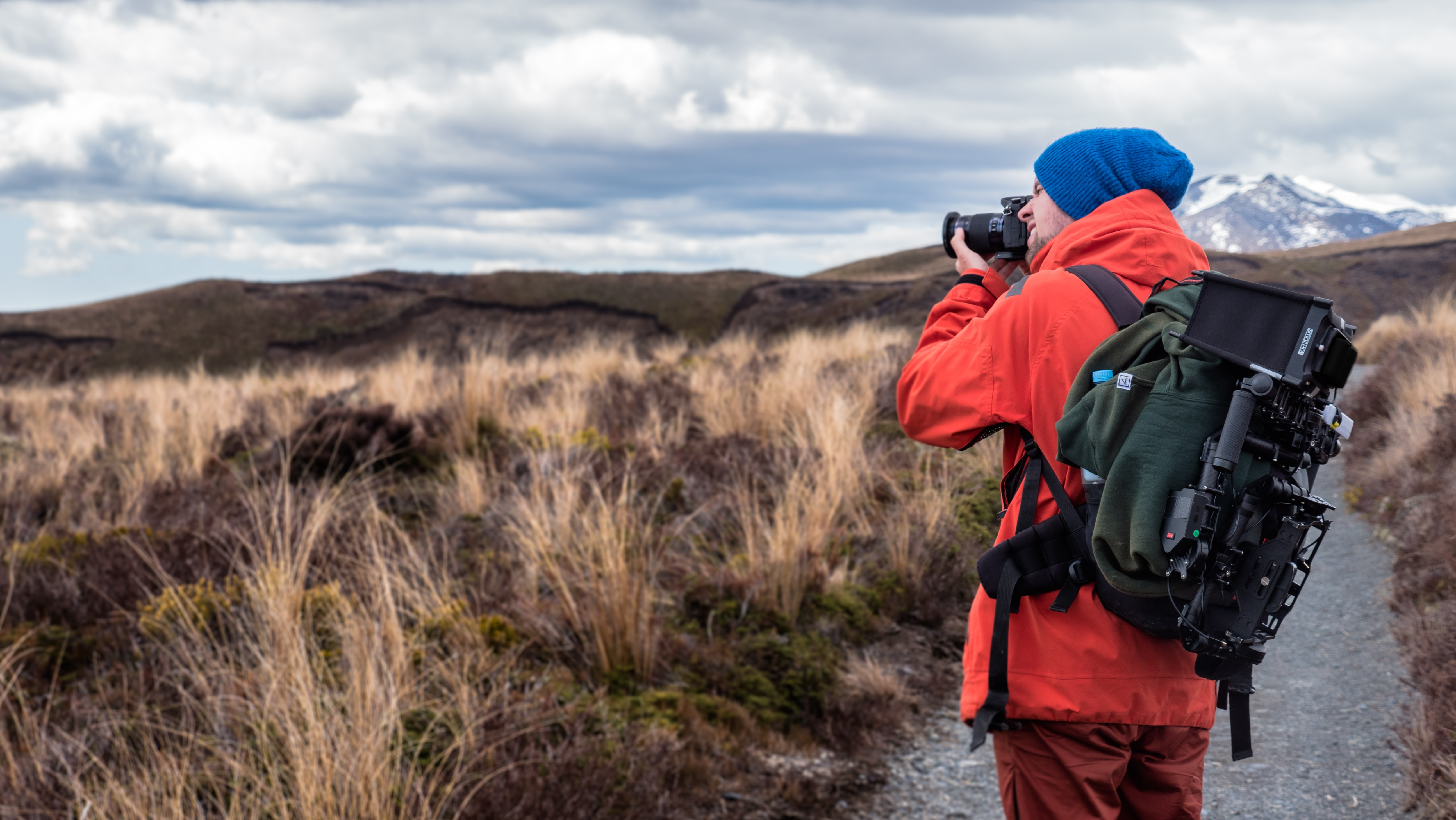 A man with photography equipment strapped to his back takes pictures of the a grassfield in the mountains