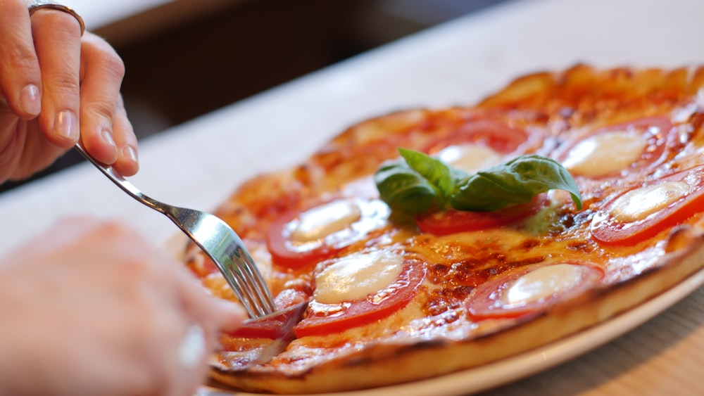 person about to slice pizza on white plate