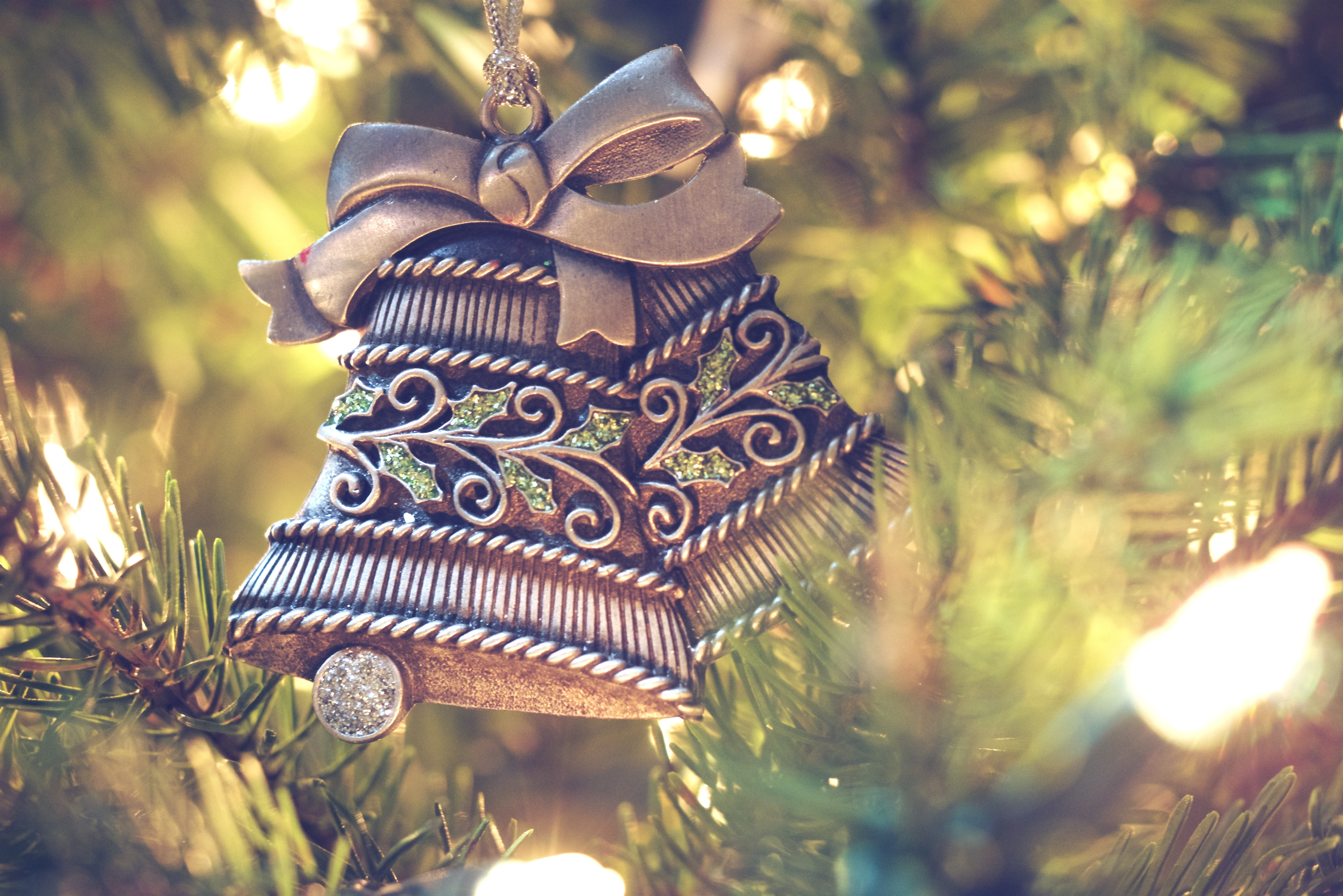 A Christmas ornament shaped like two bells hanging from a tree