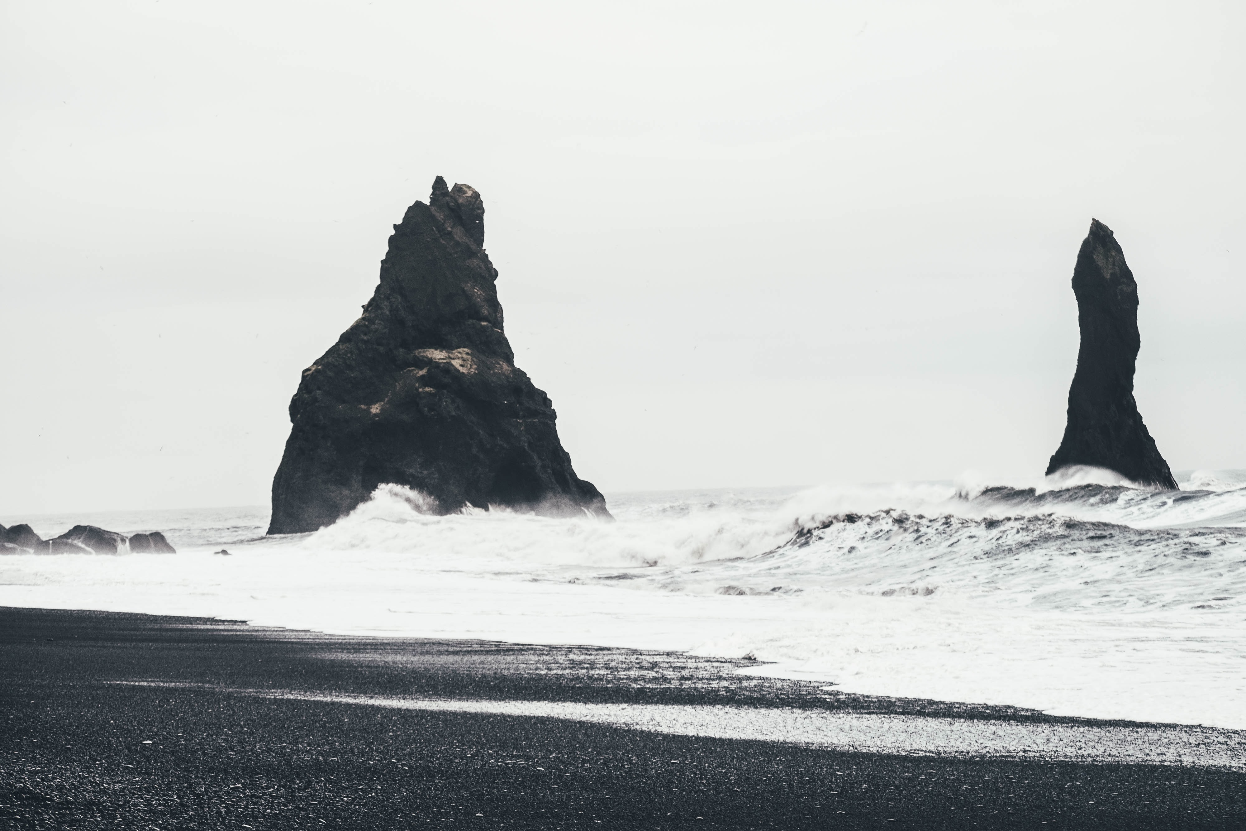 Rough sea splashing on rock formations by the black sand coastline at Reynisdrangar