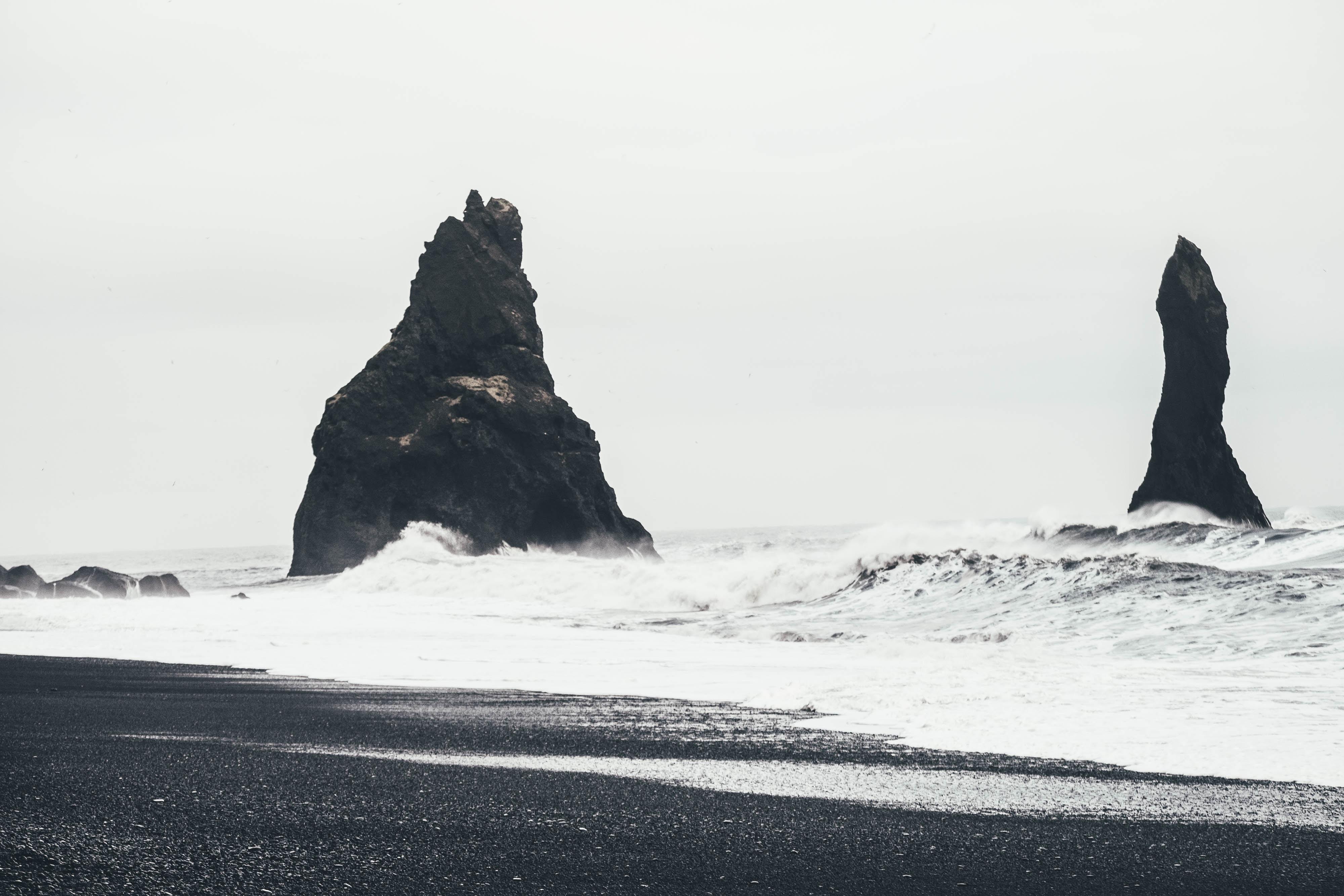 Rough sea splashing on rock formations by the black sand coastline at Reynisdrangar