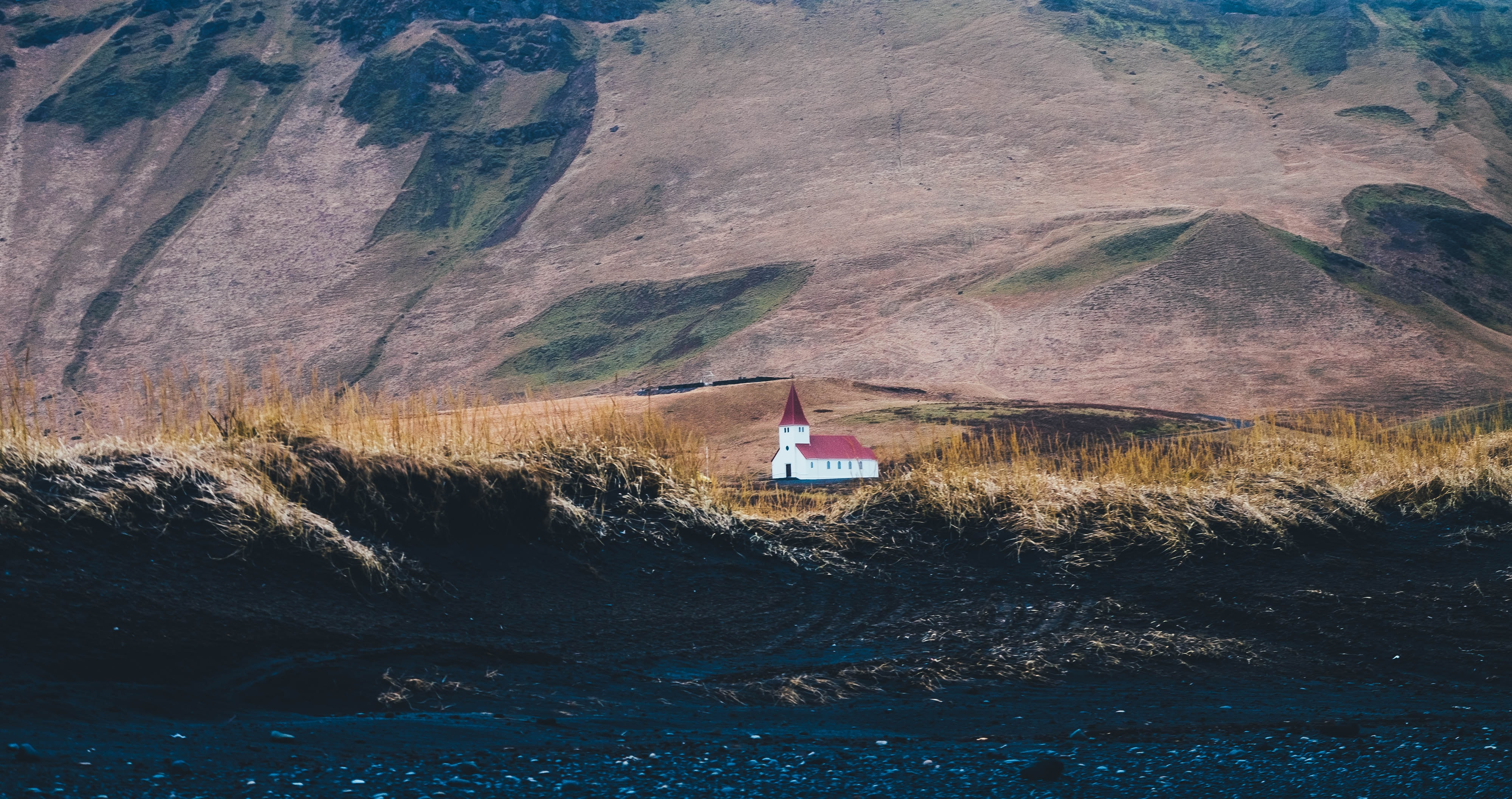 white red and chapel on grass field near mountain