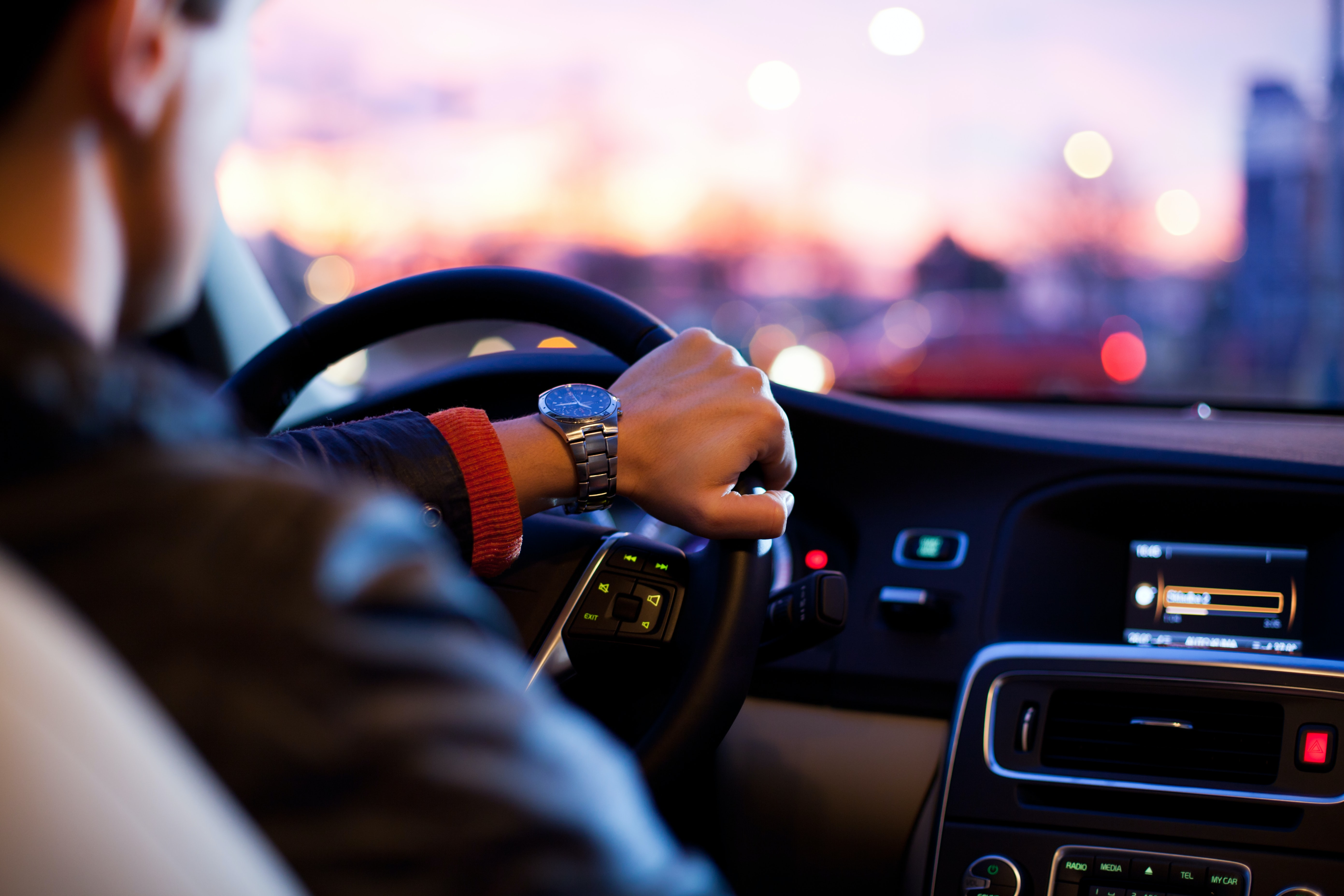 Close up of a man with watch driving a car, hand on steering wheel, dashboard lights