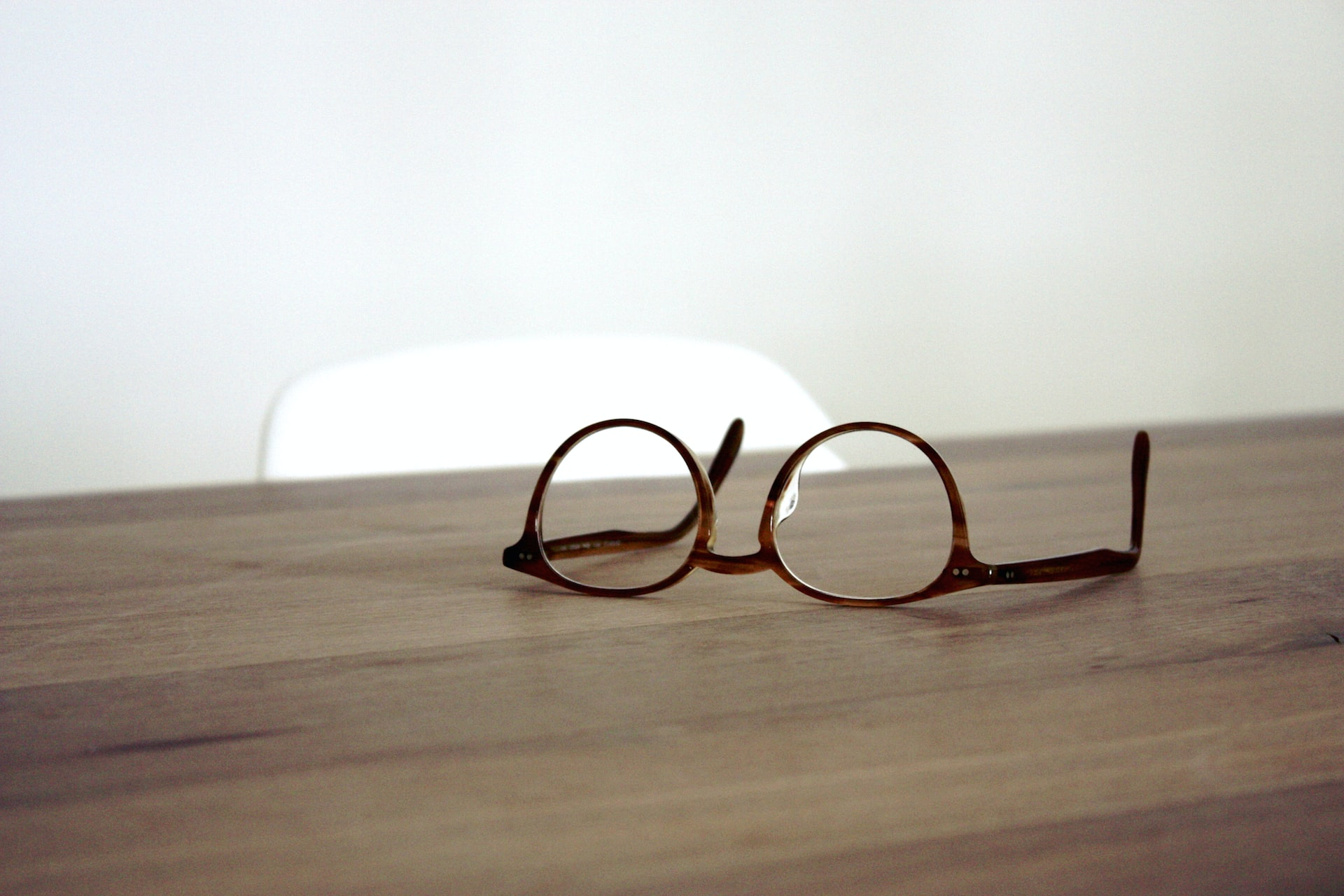 A pair of glasses on a wooden surface
