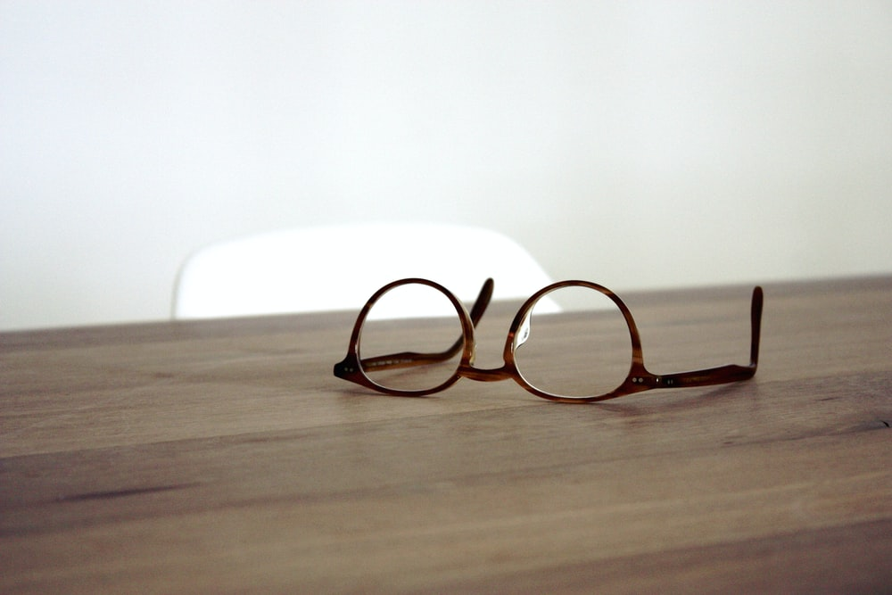 eyeglasses with brown frames on brown wooden surface