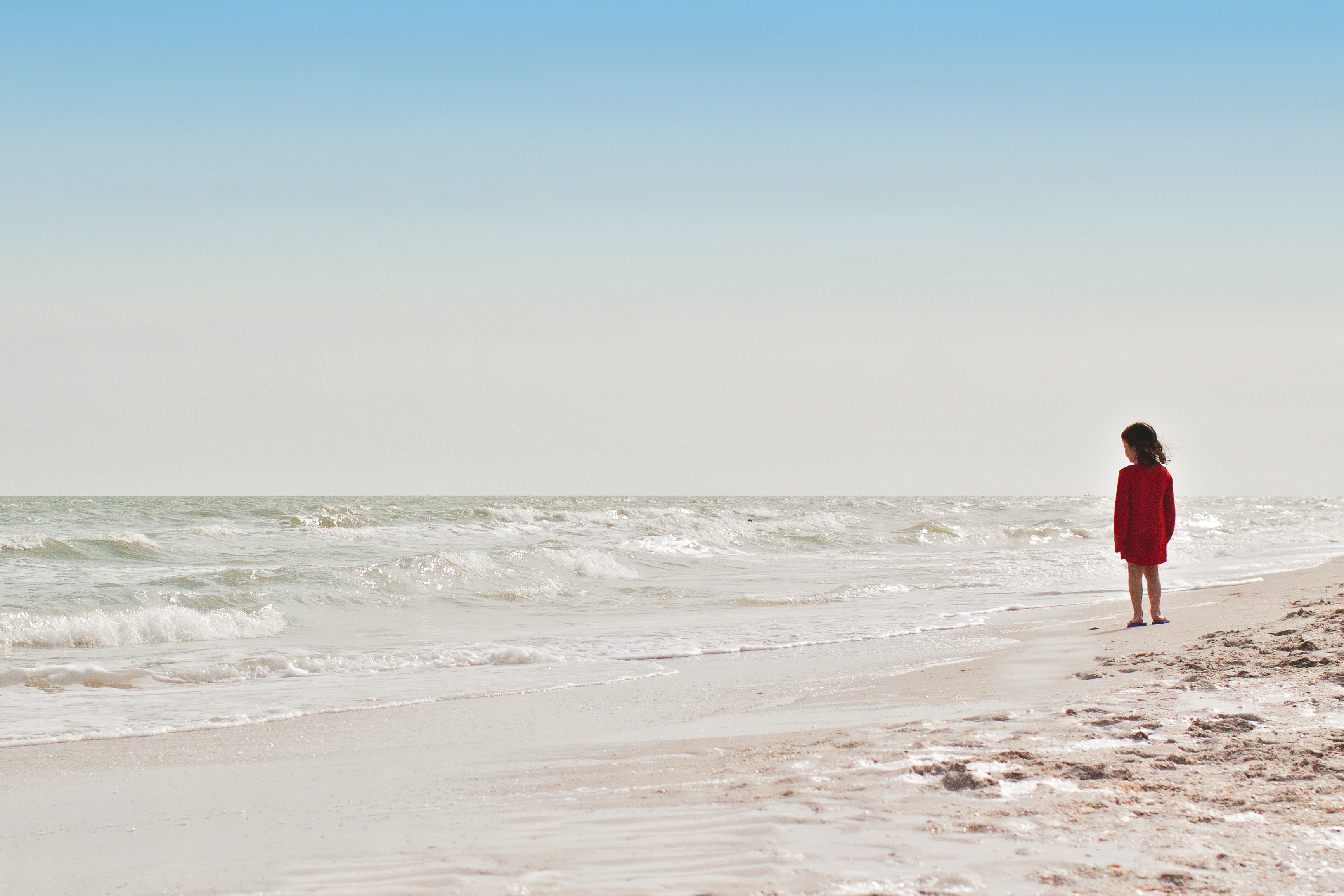 Child standing on the sandy beach looking at the ocean waves at Sanibel