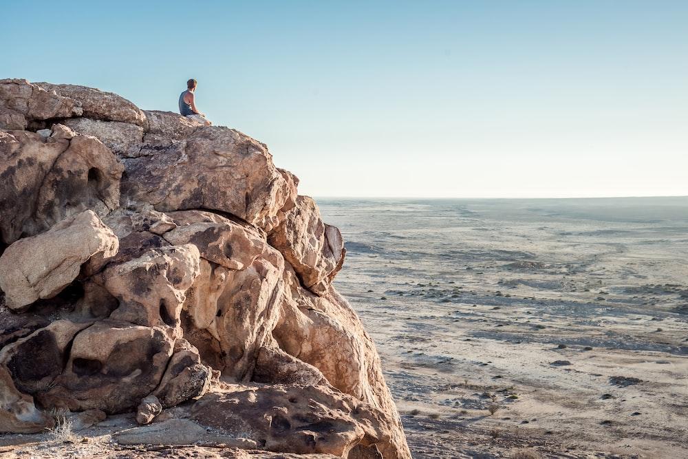 man sitting on top of rock formation near beach