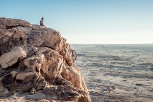 man sitting on top of rock formation near beach