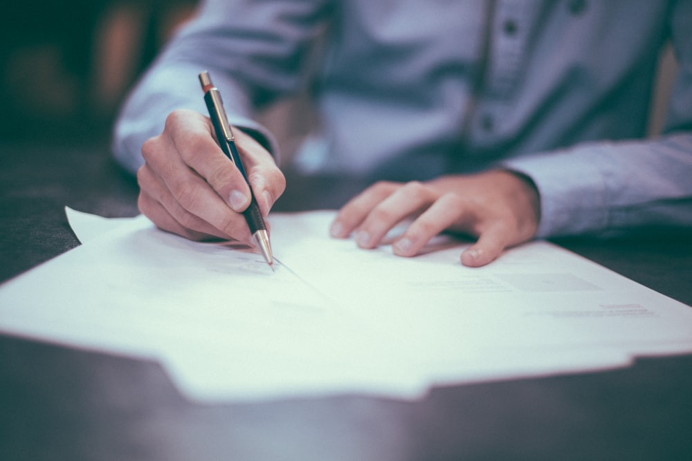 Man in a blue shirt signing some documents at a table